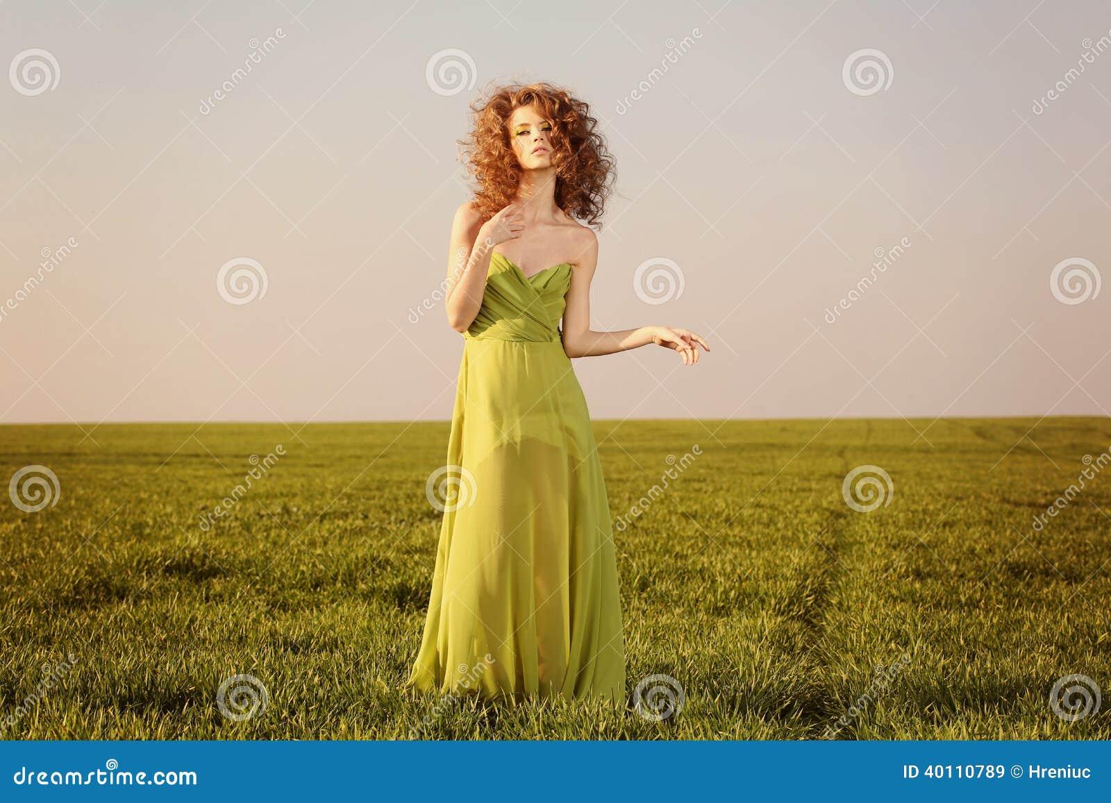 Schöne angeredete Frau mit einem Kleid des langen Grüns auf Feldern