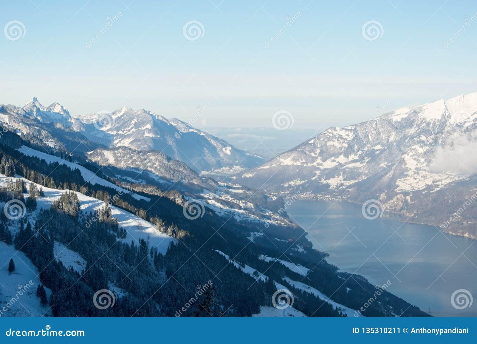 Schöne Ansicht der schneebedeckten Berge und des Sees an einem sonnigen Wintertag