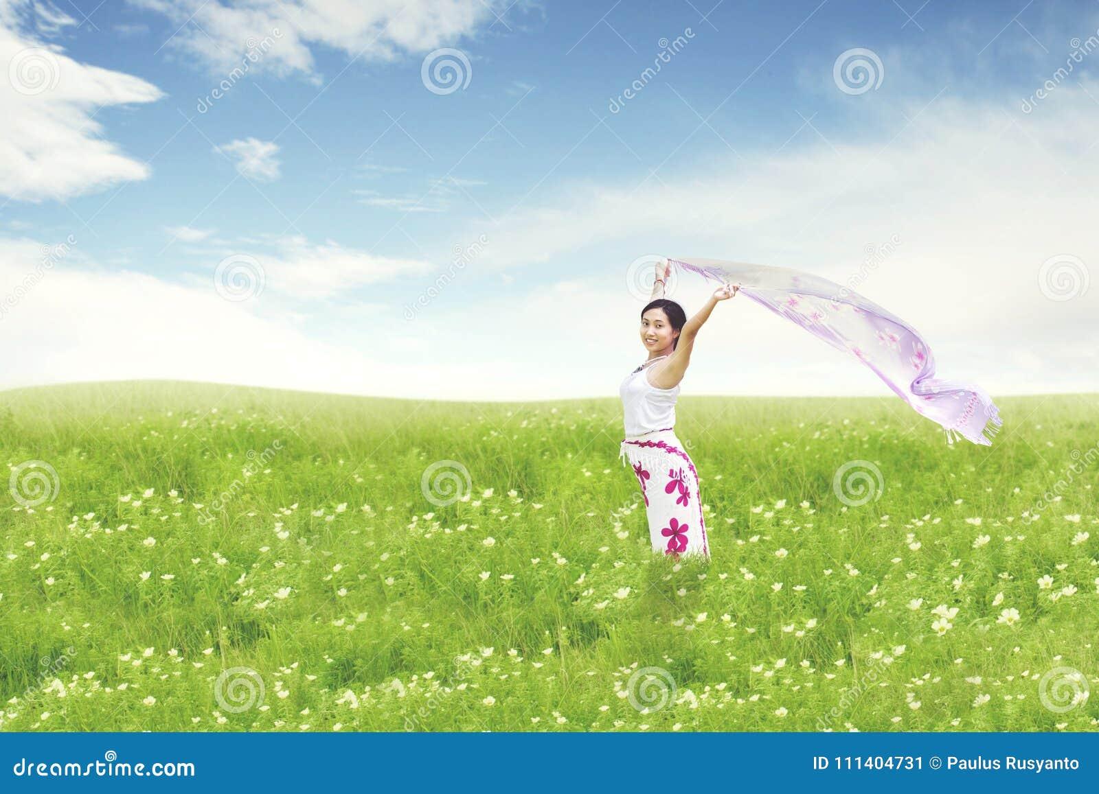 Schöne asiatische Frau, die auf Feld läuft