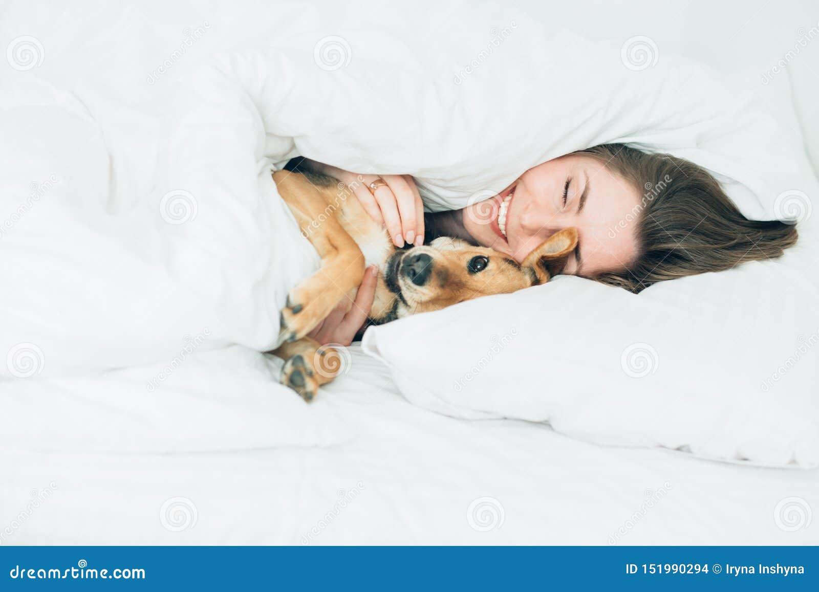 Schöne aufgeregte junge Frau und ihr netter Kanaillehund sind täuschen herum und betrachten Kamera beim Lügen, das mit einer Deck