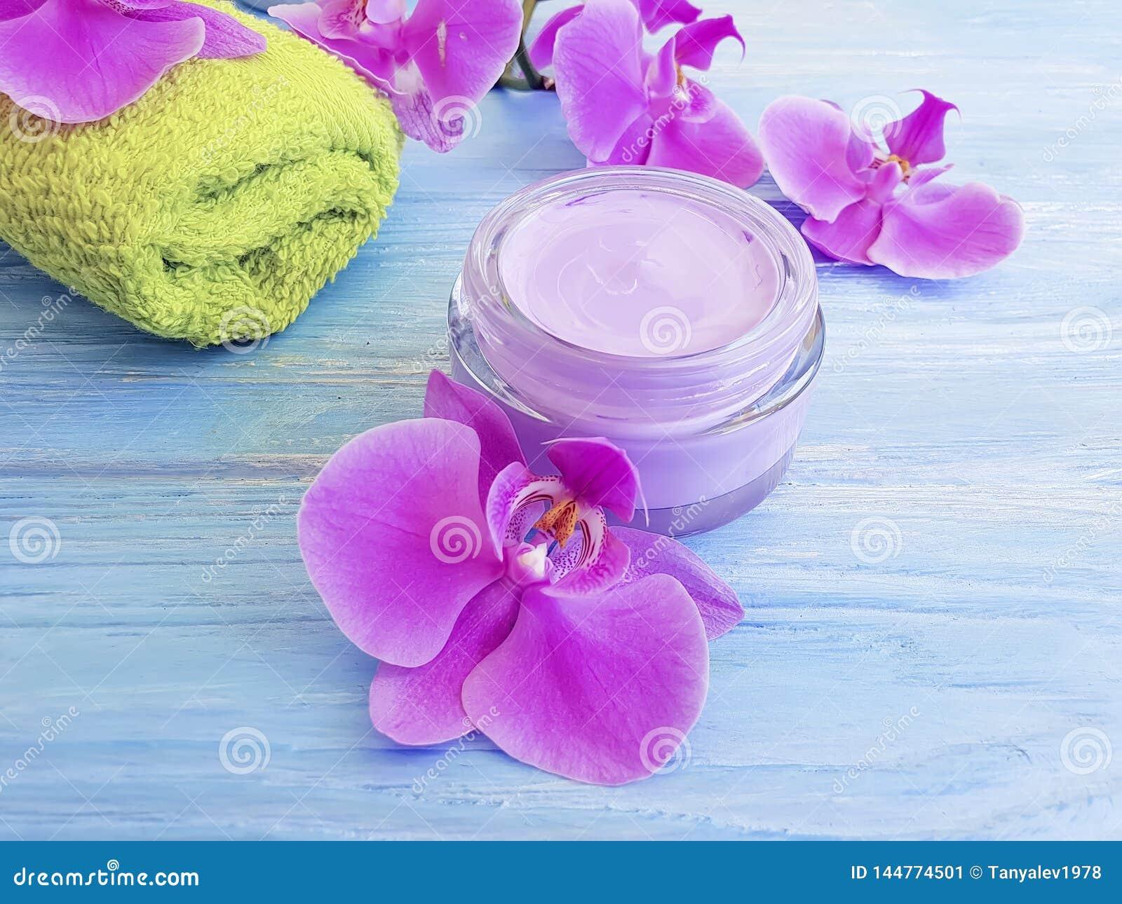 Schöne Behandlung des kosmetischen natürlichen Reiniger-Sahnefrühlinges der Orchideenblume auf hölzernem Hintergrund