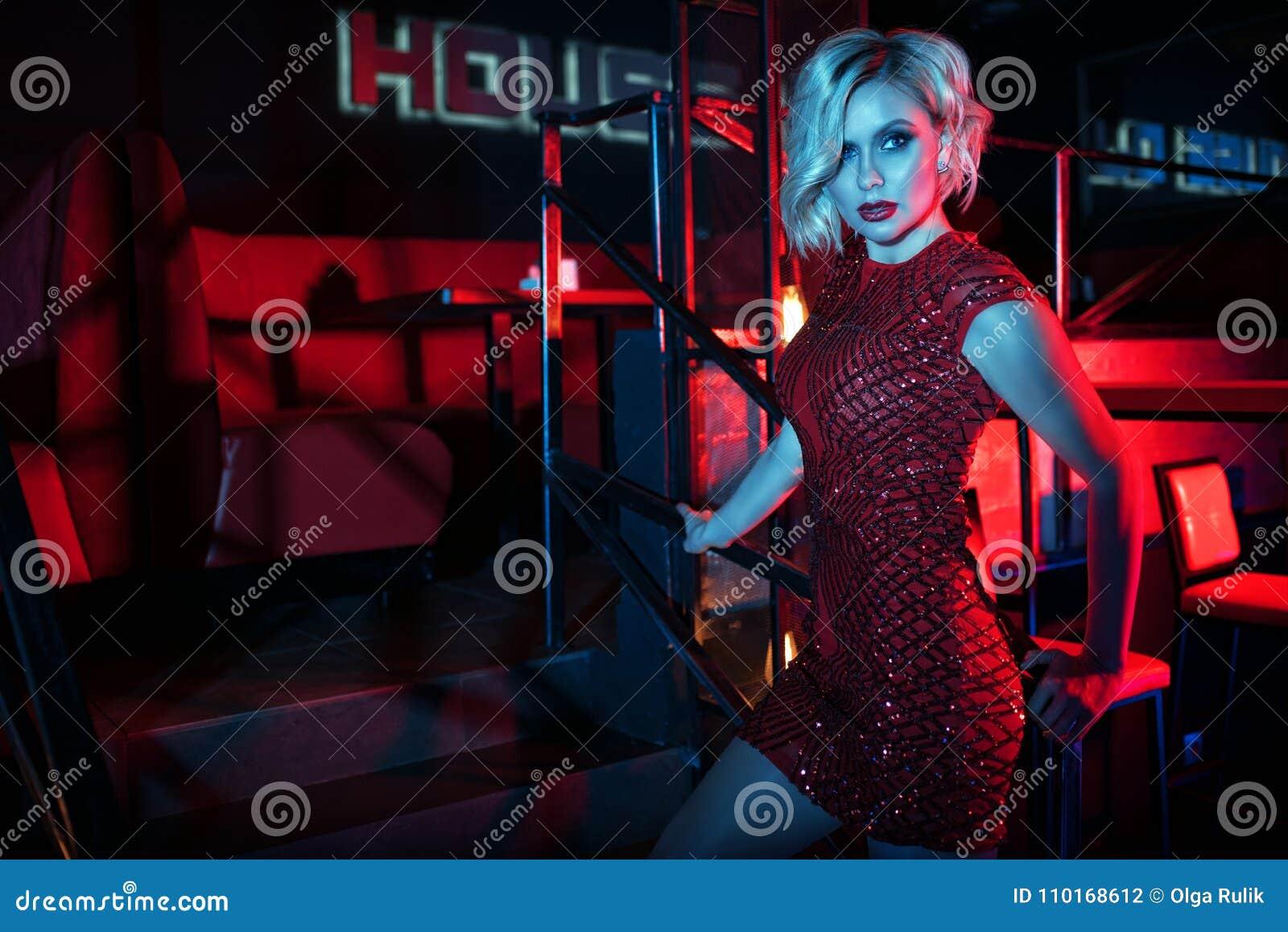 Schöne bezaubernde blonde Frau, die auf der Treppe im Nachtclub in den bunten Neonlichtern steht