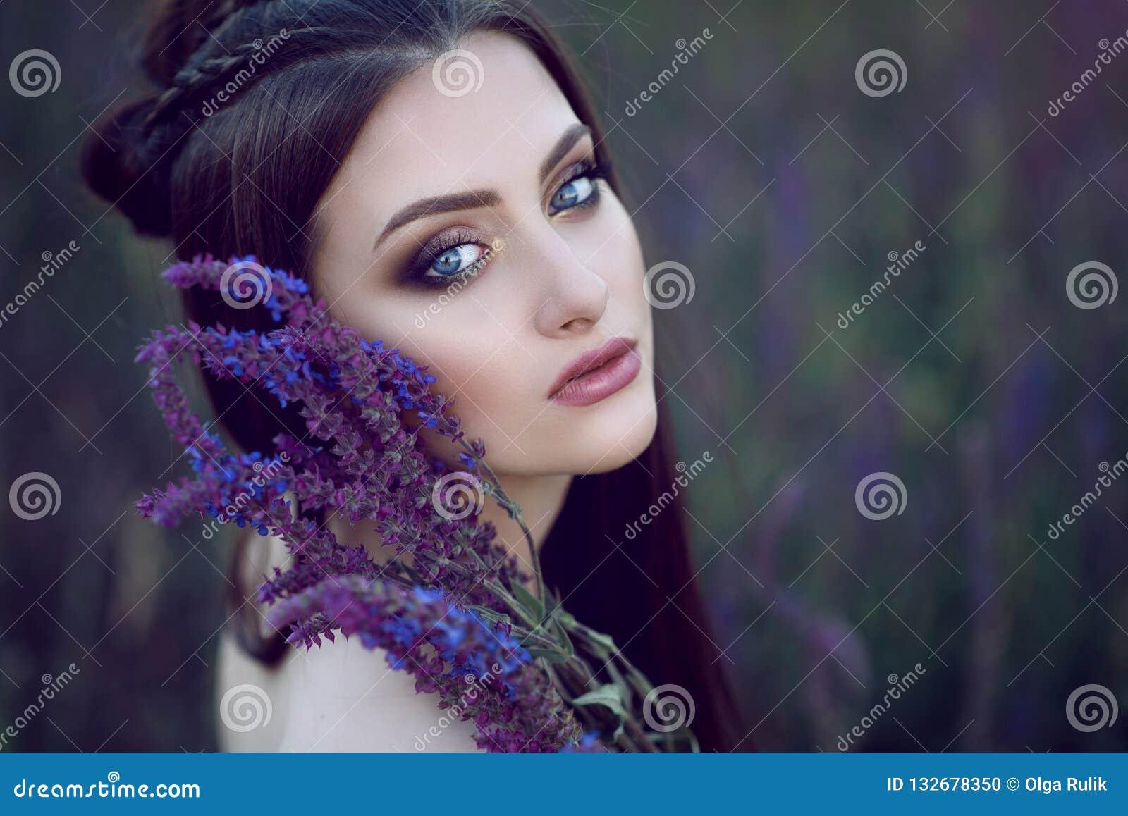 Schöne blauäugige Dame mit perfektem bilden und die geflochtene Frisur, die auf dem Gebiet sitzt und purpurrote Blumen an ihrem G