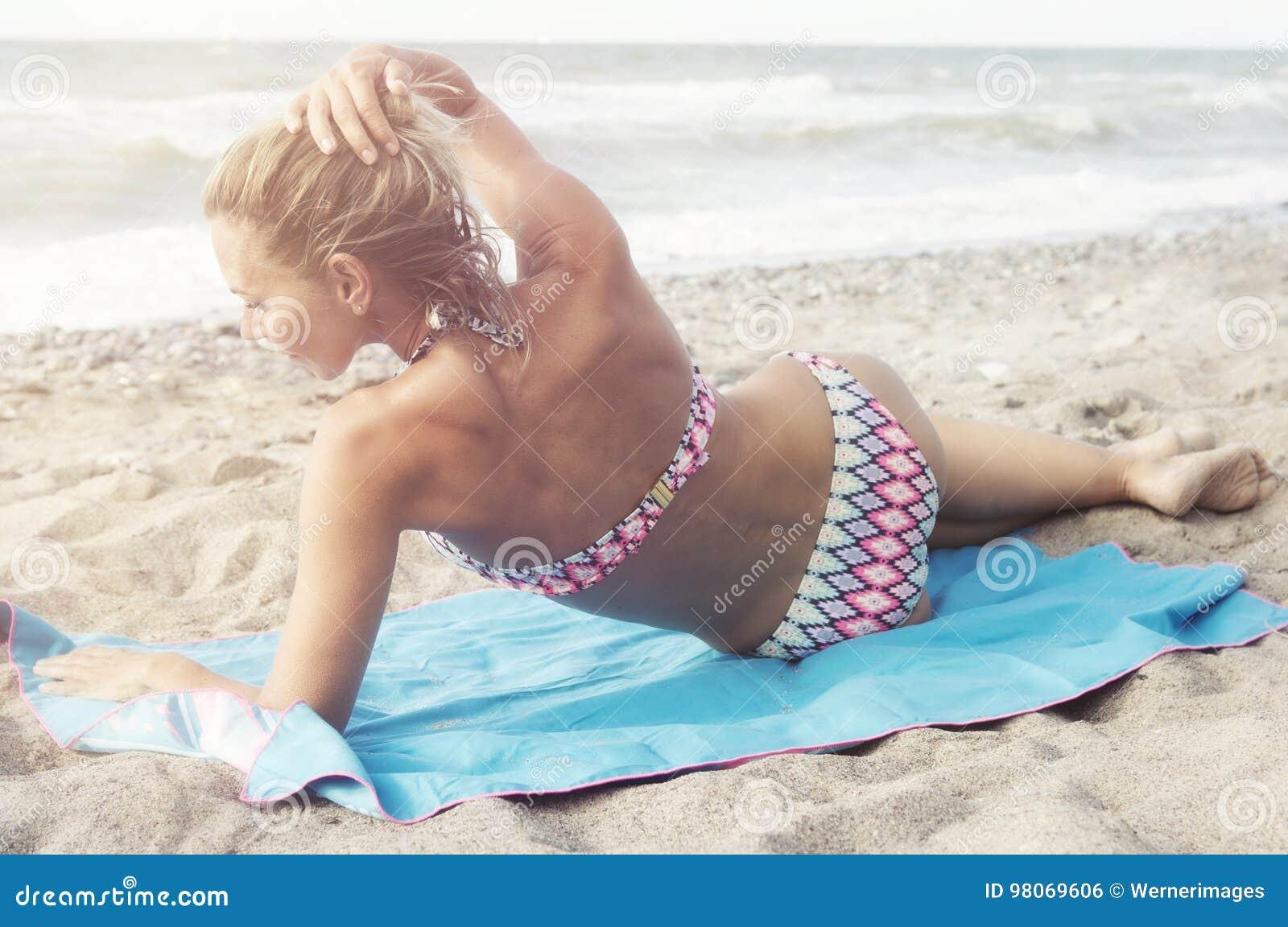 Schöne blonde Frau im Bikini, der auf dem Strand liegt