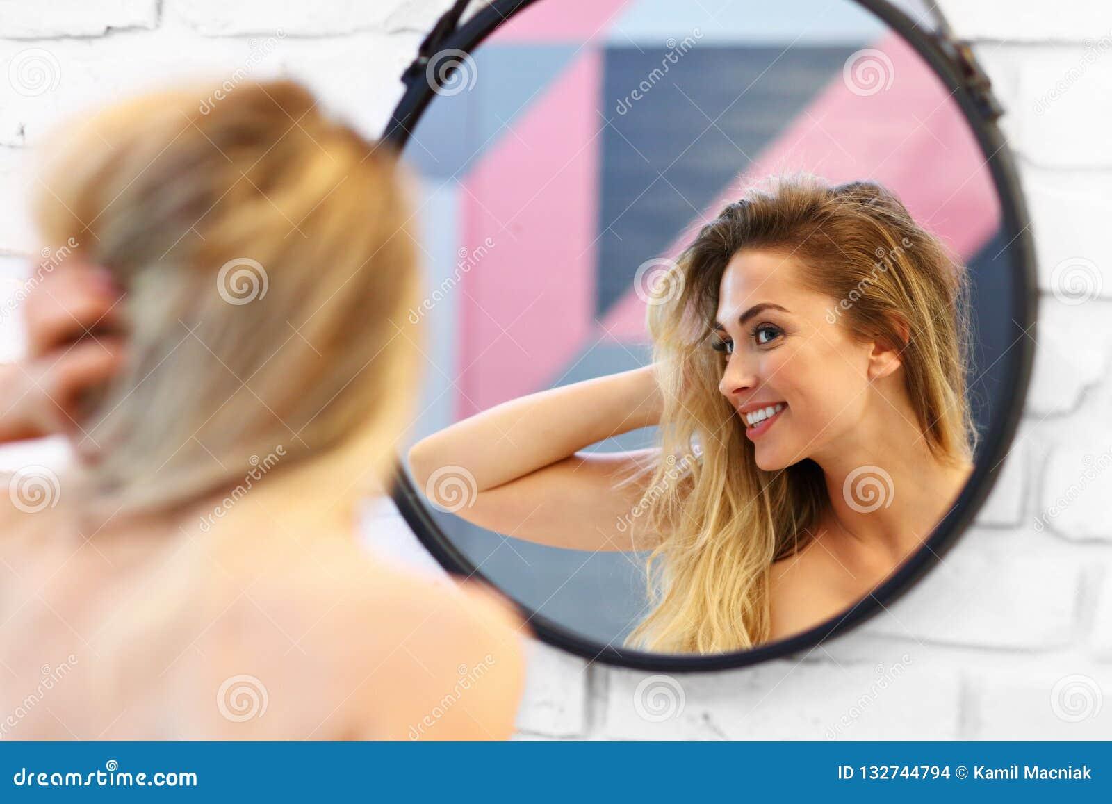 Schöne blonde kaukasische Frau, die im Badezimmer mit dem nass Haar aufwirft