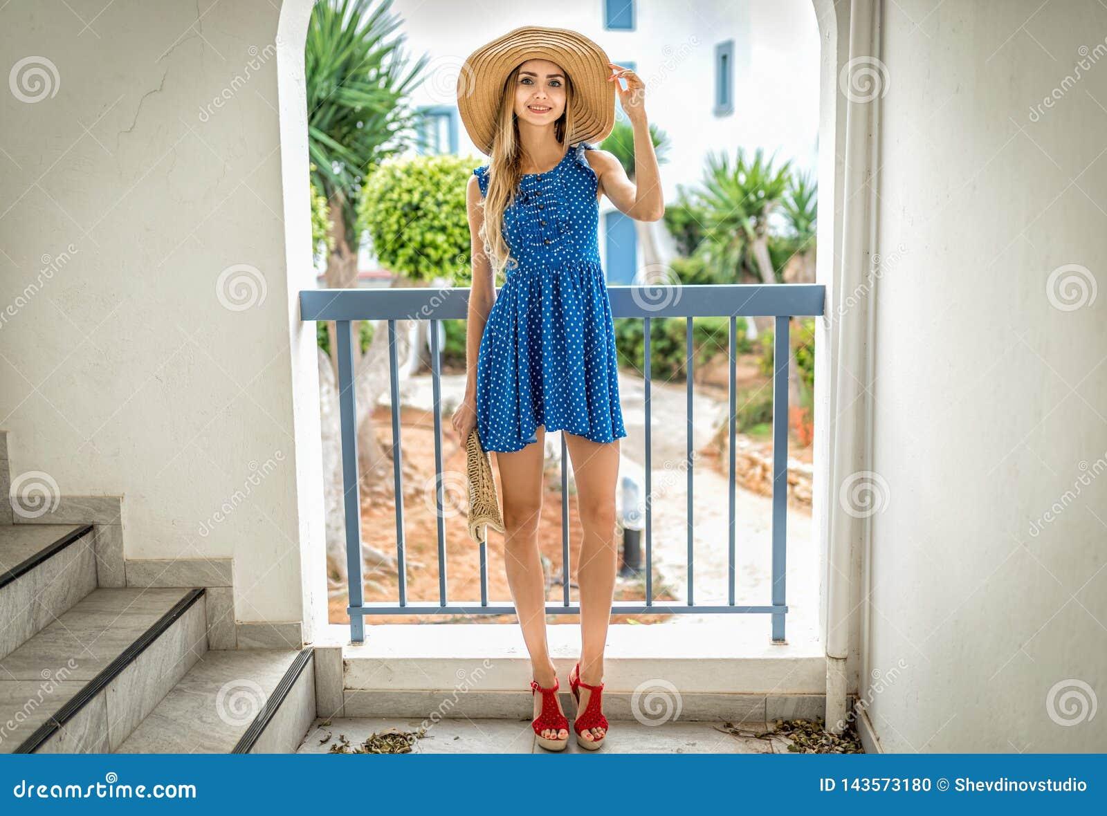 Schöne Blondine im Kleid mit Strohhutsommermode in Santorini