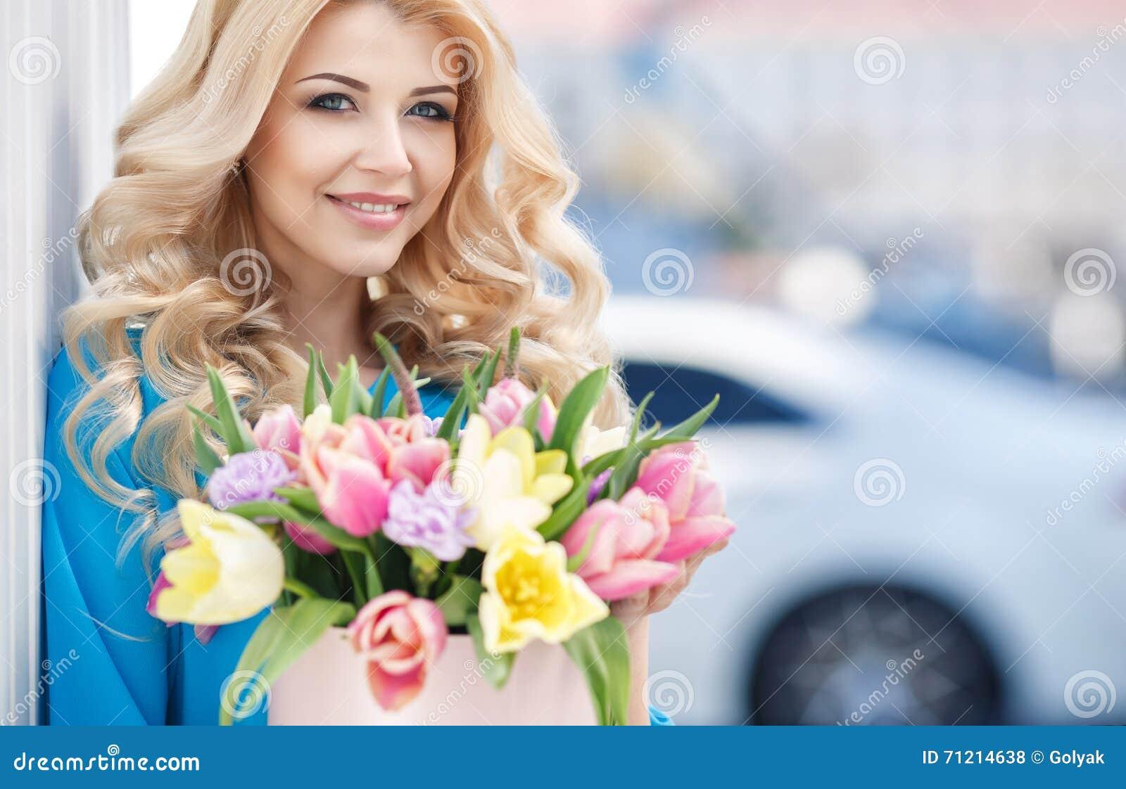 Schöne Blondine mit Blumen in der Geschenkbox