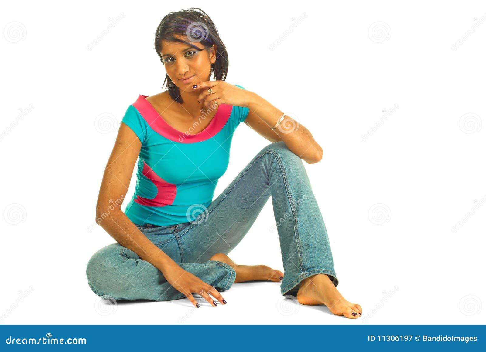 Schöne braune Frau, die auf dem Fußboden sitzt