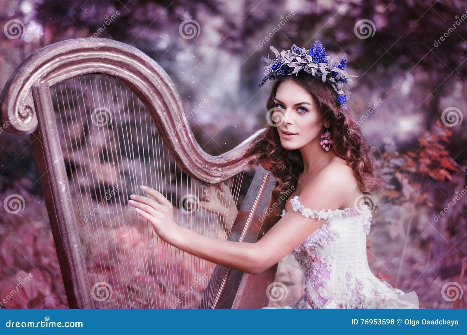 Schöne braunhaarige Frau mit einem Blumenkranz auf ihrem Kopf, ein weißes Kleid tragend, welches die Harfe im Wald spielt