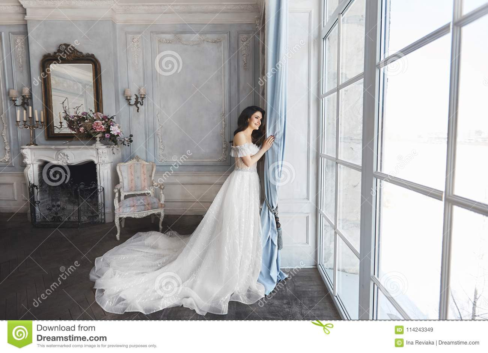 Schöne Braut, junge vorbildliche Brunettefrau, im stilvollen Hochzeitskleid mit nackten Schultern, mit Blumenstrauß von Blumen he