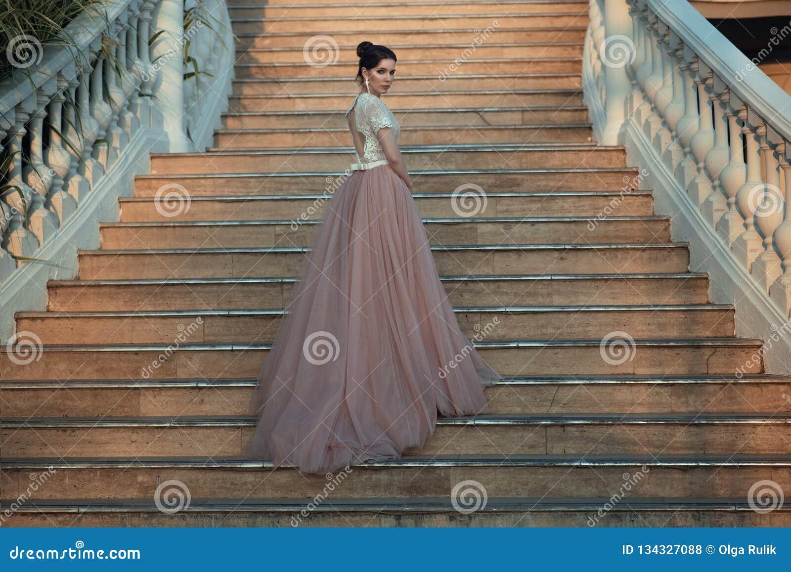 Schöne Dame im luxuriösen Ballsaalkleid gehend herauf die Treppe ihres Palastes