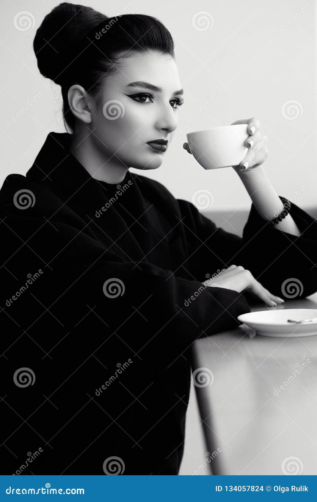 Schöne Dame mit perfektem bilden und das Haar, das zurück in ein hohes Brötchen ausrangiert wird, das an der Bar und am trinkende