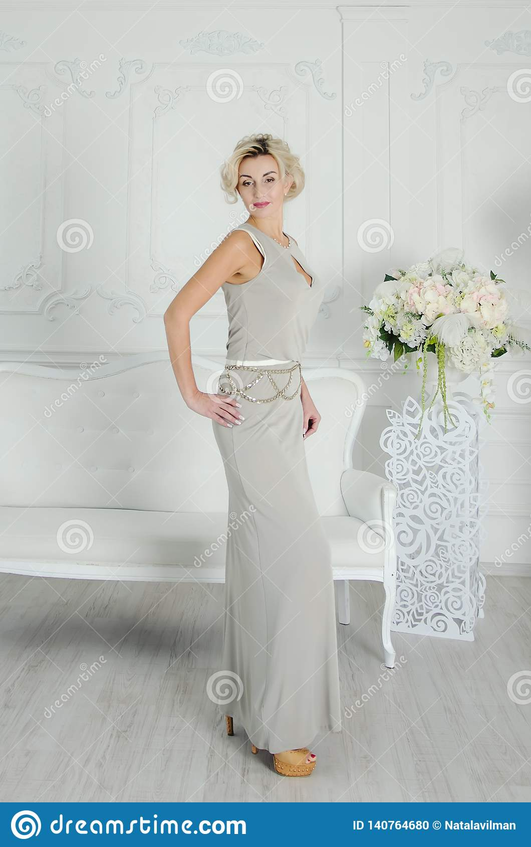 Schöne Dame von 40 Jahren in einem langen Glättungskleid Schicker Innenraum in der hellen Farbe