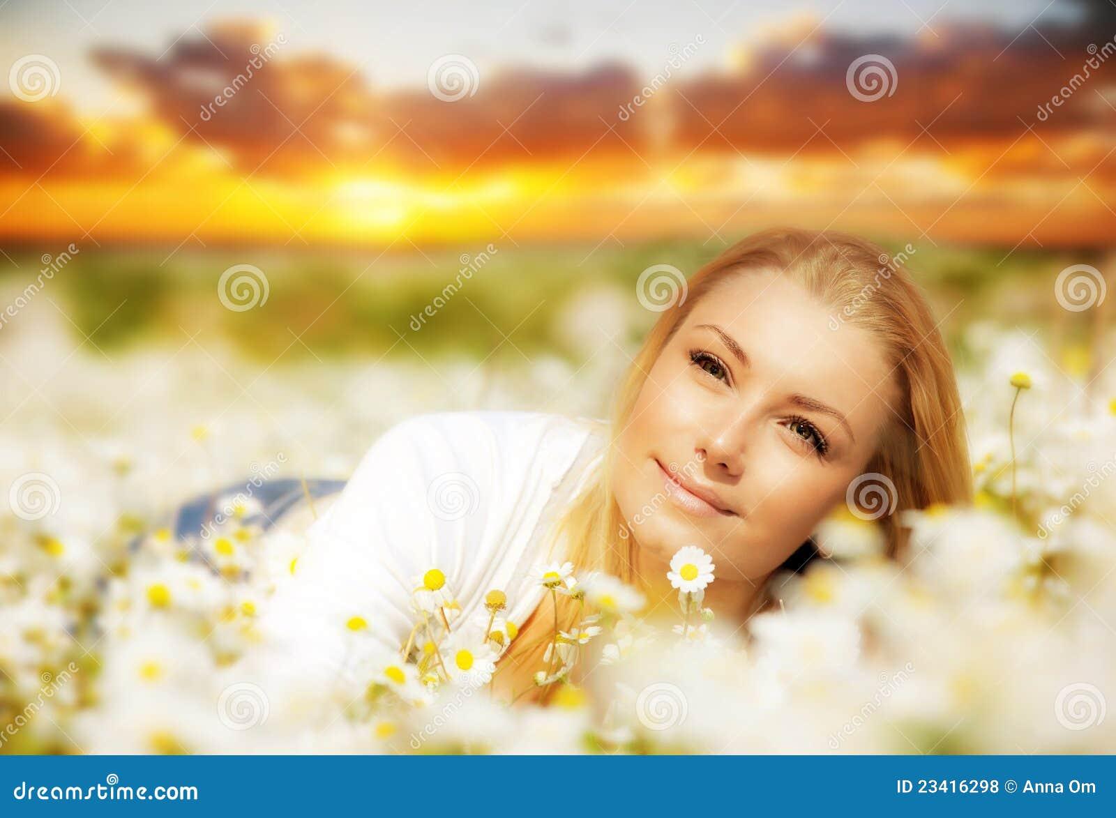 Schöne Frau, die Blumenfeld auf Sonnenuntergang genießt