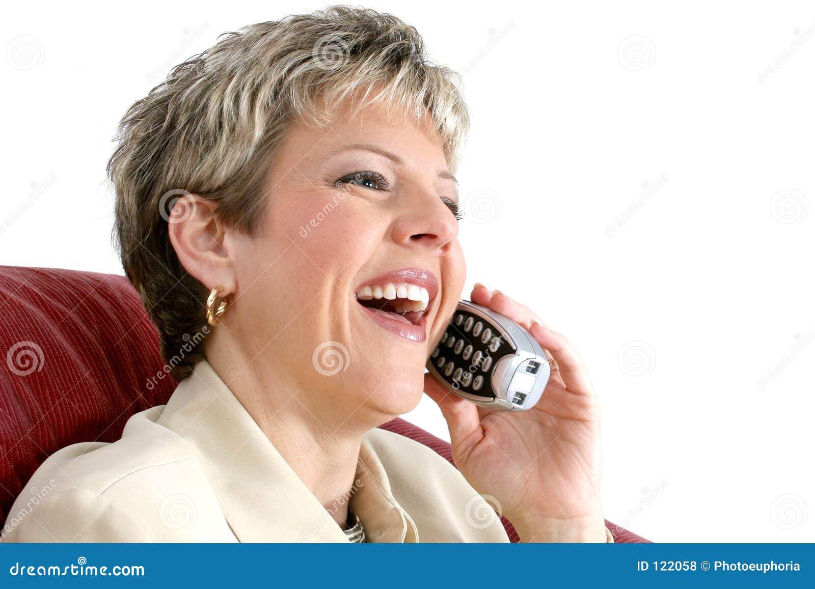 Schöne Frau, die an einem drahtlosen Haus-Telefon über Weiß spricht