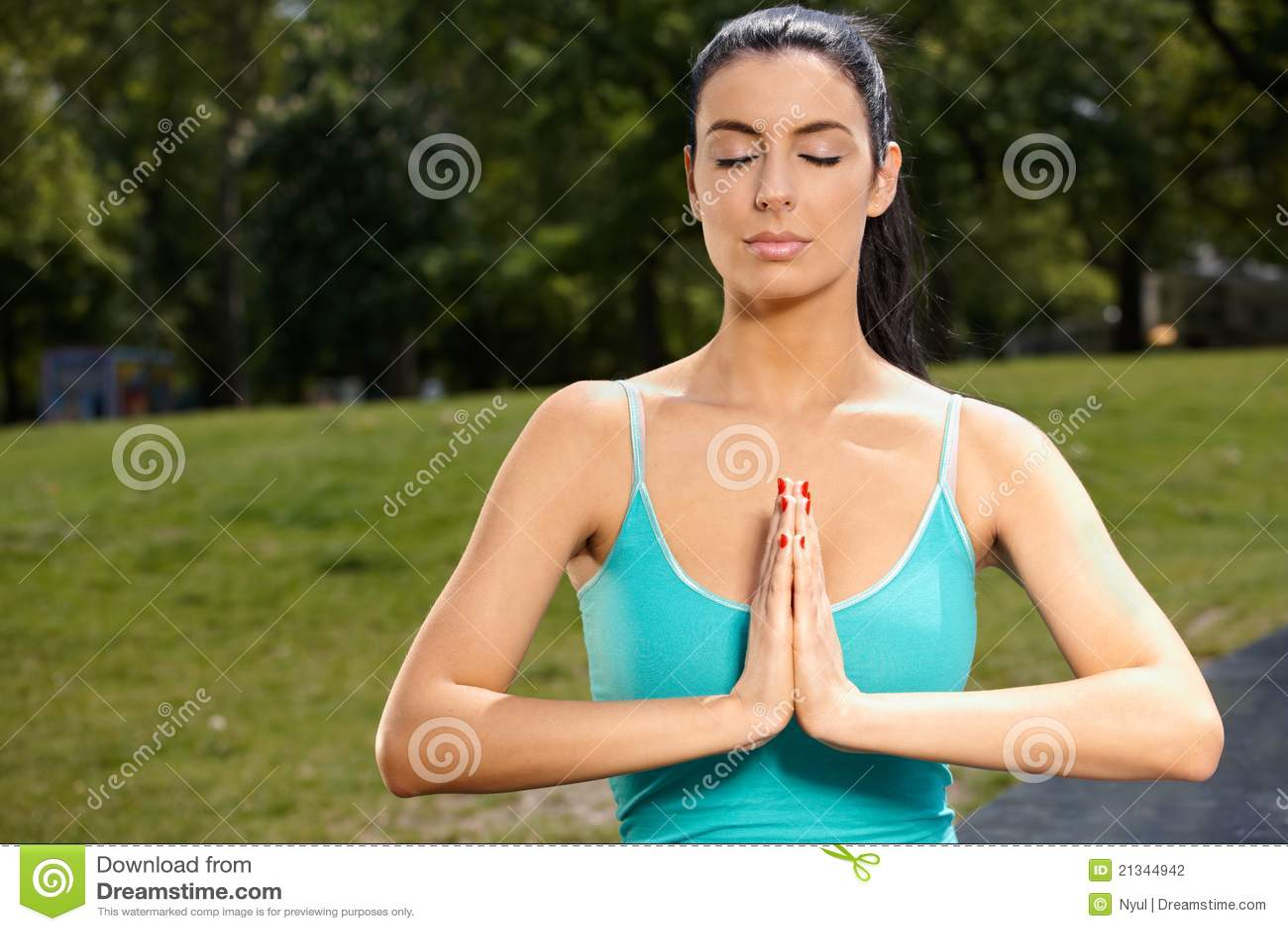 Schöne Frau, die im Park meditiert