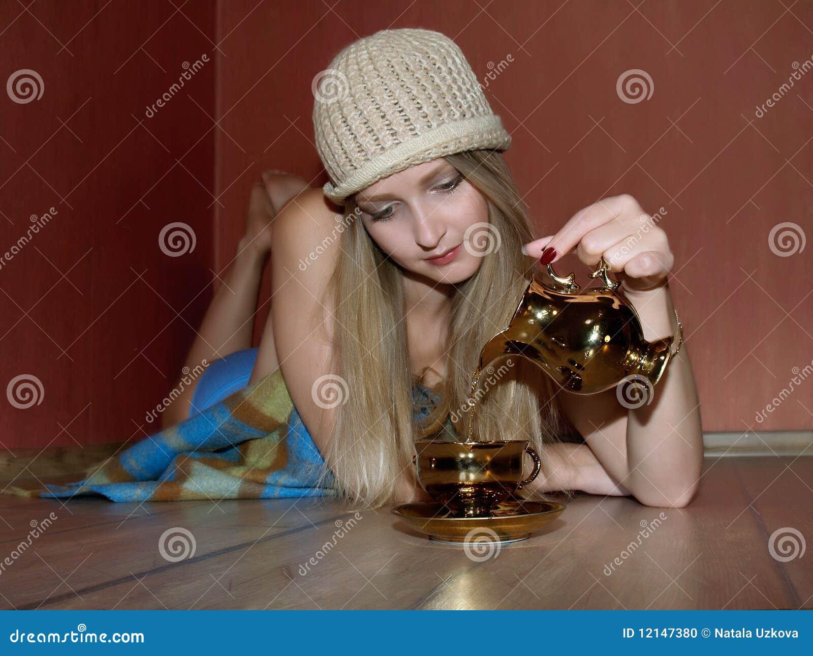 Schöne Frau, die sich zu Hause mit einer Tasse Tee entspannt
