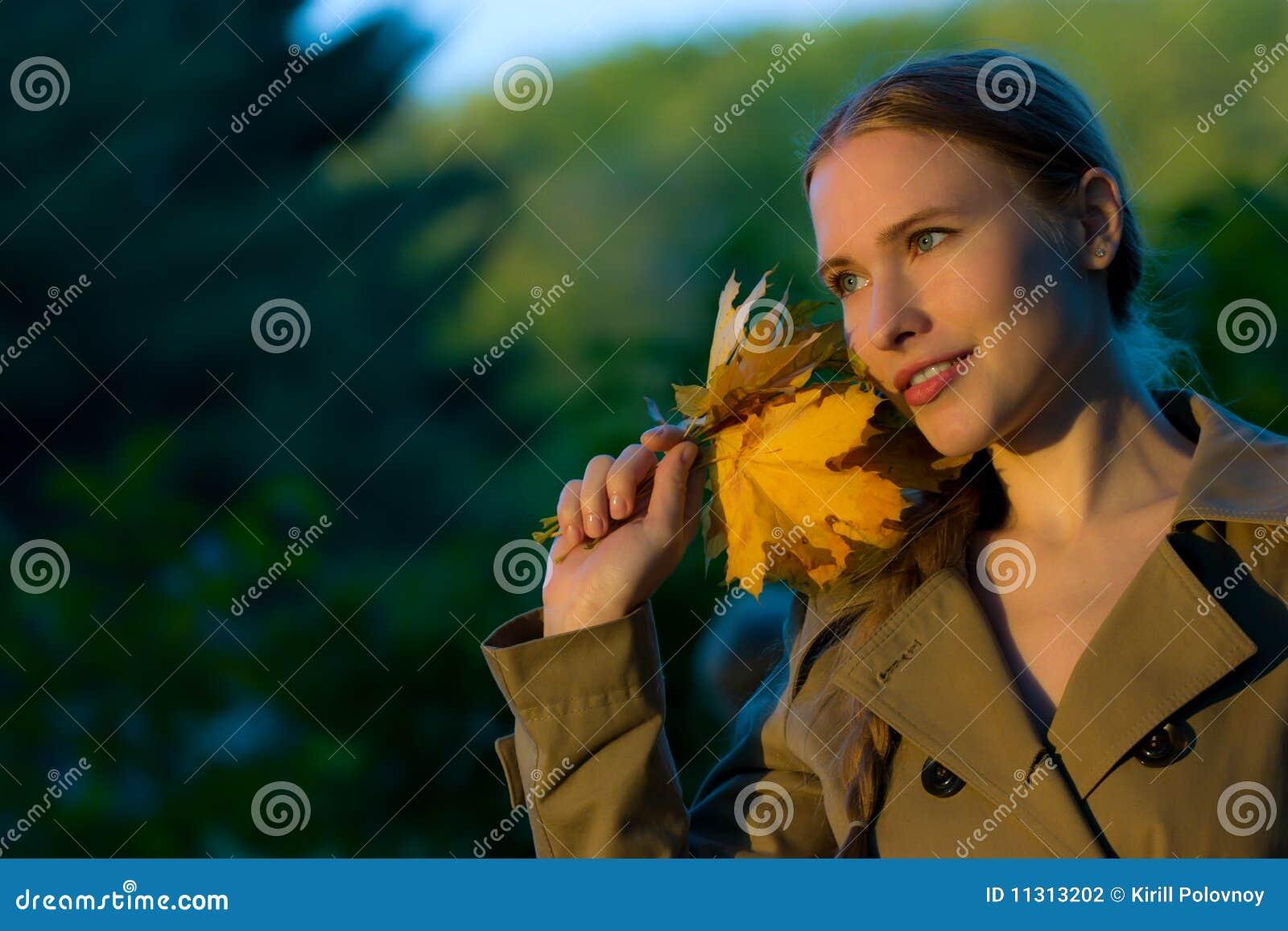 Schöne Frau mit gelben Blättern