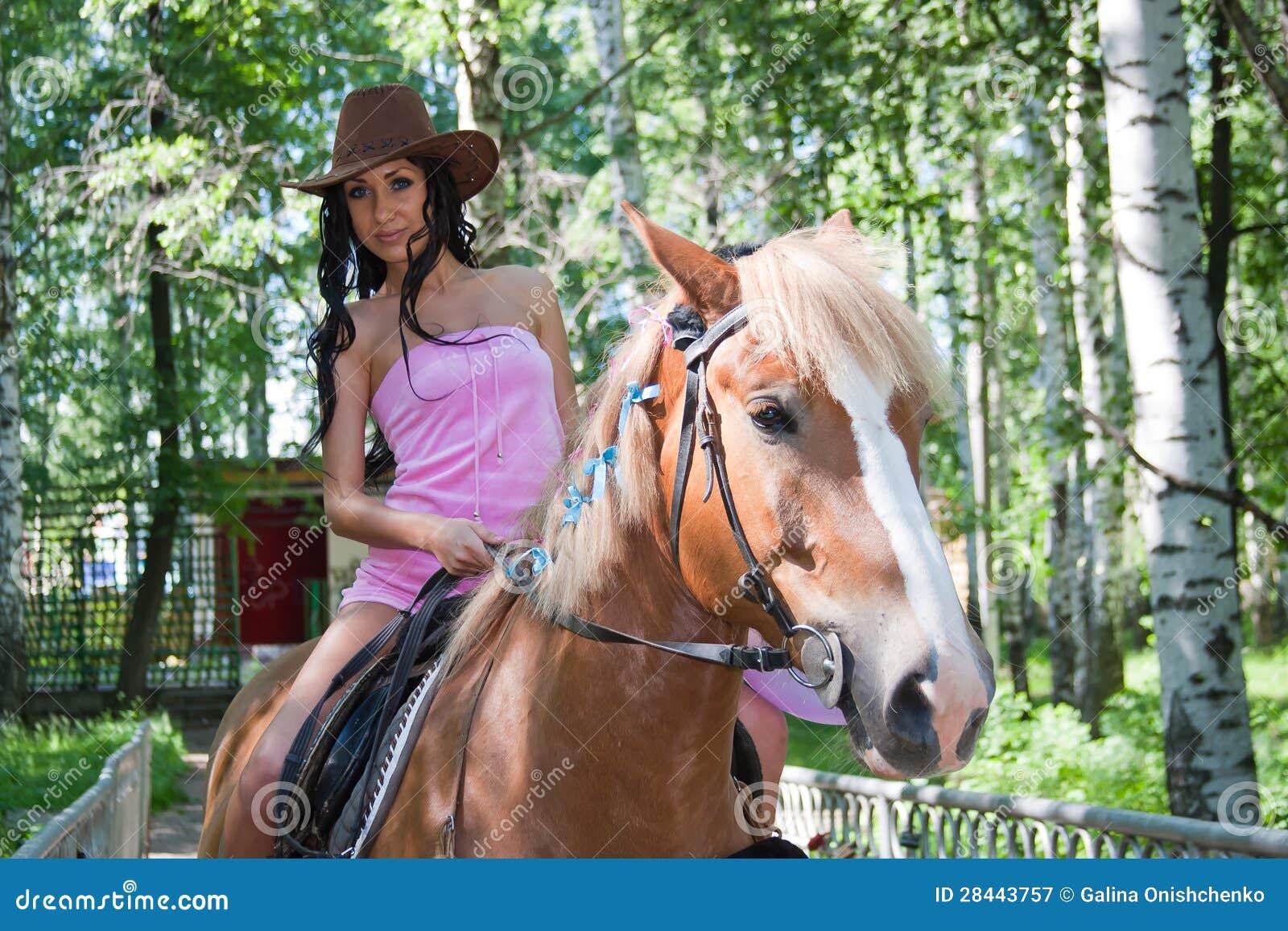 Schöne Frau sitzt mit gespreizten Beinen auf einem Pferd