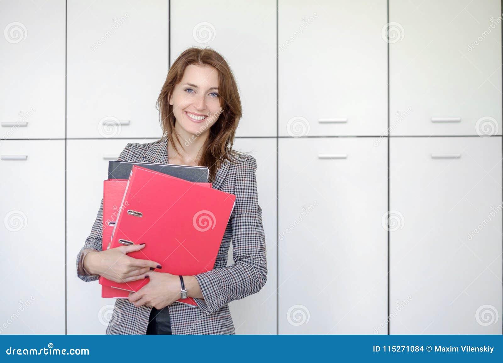 Schöne Geschäftsfrau steht mit einem roten Ordner in den Händen in einem Büro