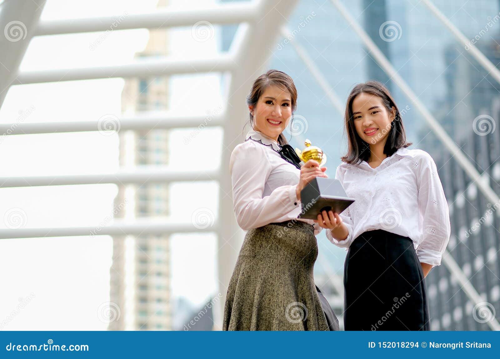 Schöne Geschäftsmädchen zeigen ihre Trophäe des Erfolgs in ihren Arbeiten und stehen unter dem hohen Gebäude in der Stadt
