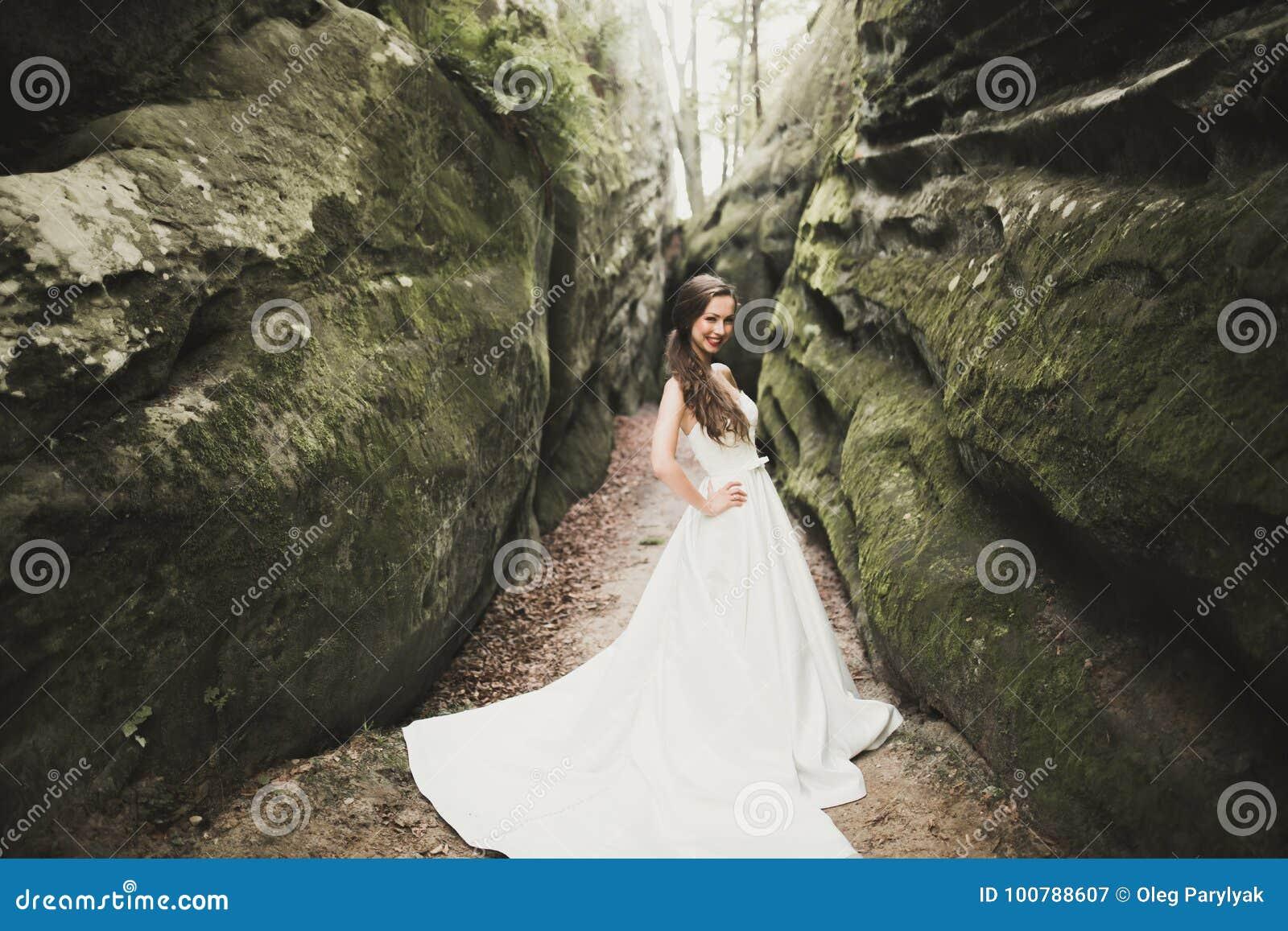 Schöne glückliche Braut draußen in einem Wald mit Felsen Hochzeitsperfekter tag