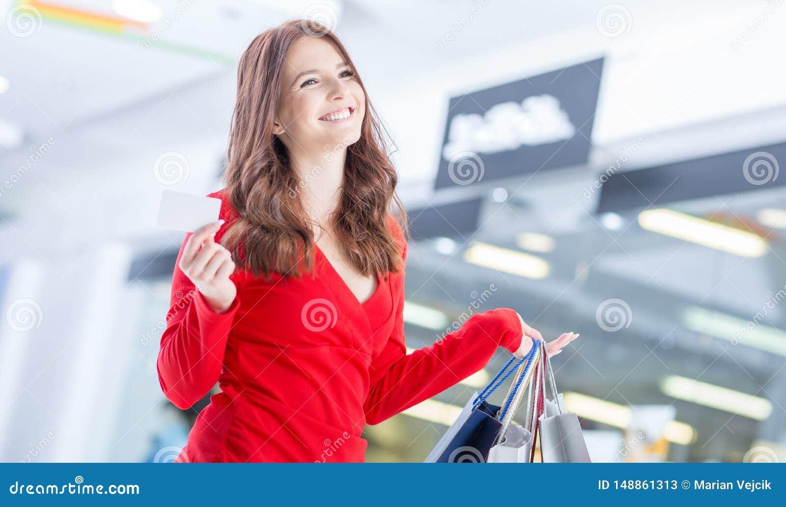 Sch?ne gl?ckliche Frau mit Kreditkarte und Einkaufstaschen im Einkaufszentrum