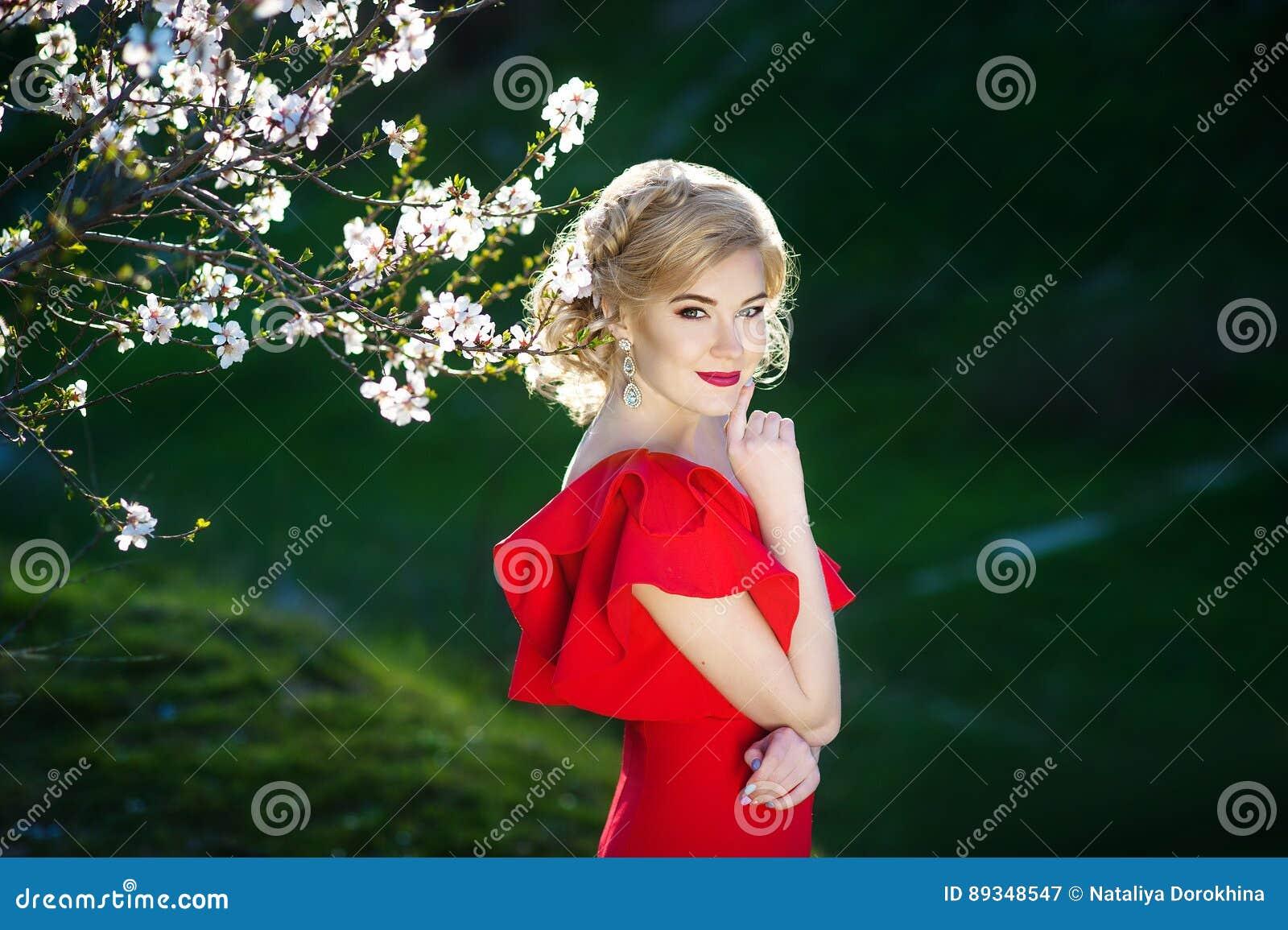 Schöne glückliche junge Frau, die Geruch in einem blühenden Frühlingsgarten genießt
