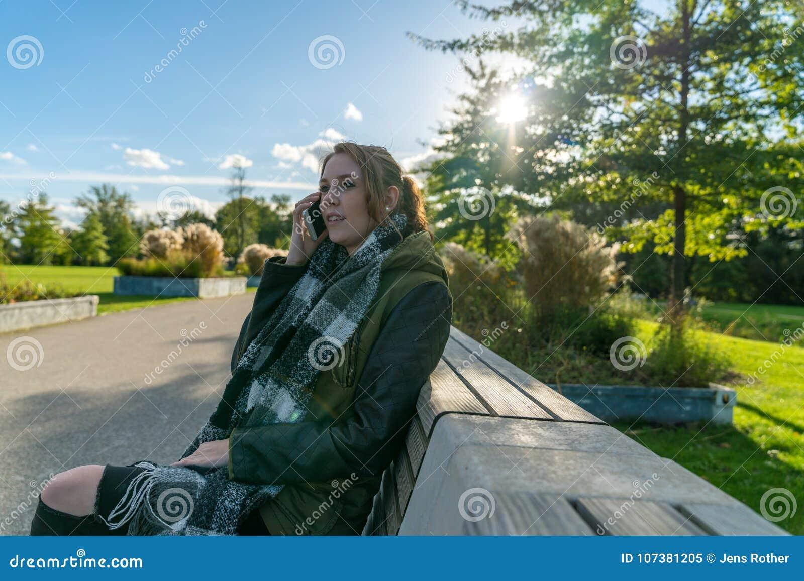 Schöne glückliche lächelnde junge Frau, die Handy verwendet