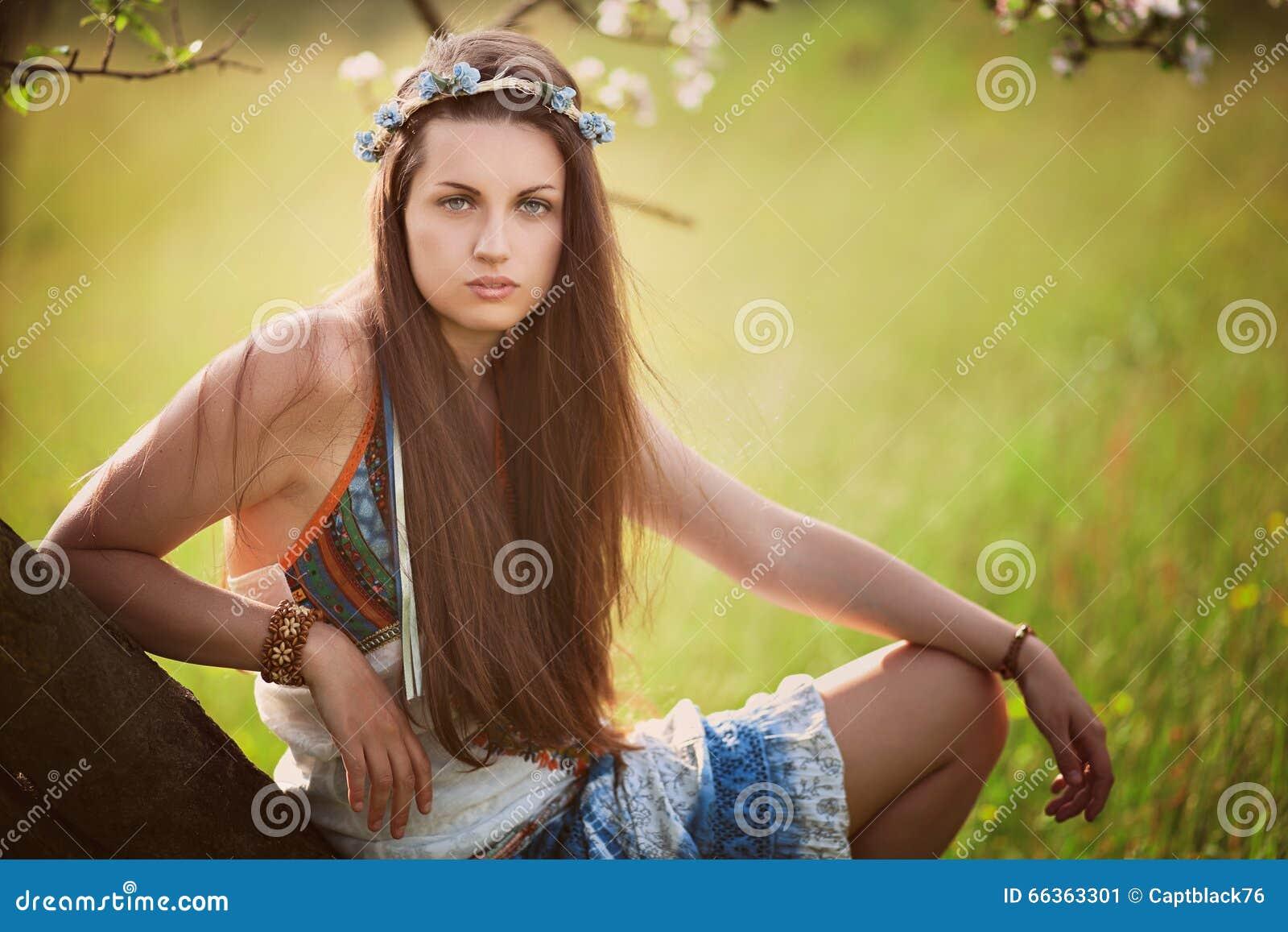 Schöne Hippiefrau, die auf einem Baum sich lehnt