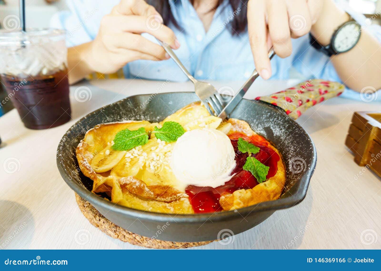 Schöne junge Asiatin genießen, selbst gemachte Fruchtpfannkuchen mit Banane, Erdbeere, Eiscreme und gefrorenem Kaffee zu essen Kö