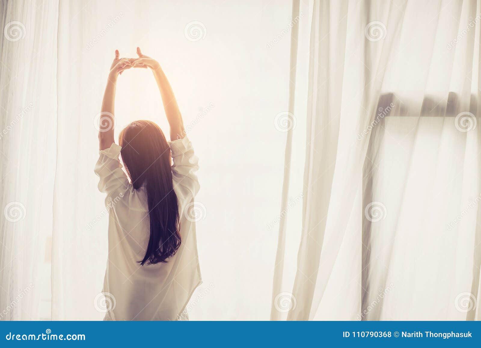 Schöne junge asiatische Frauenausdehnung und entspannen sich im Bett nach aufwachen Morgen am Schlafzimmer