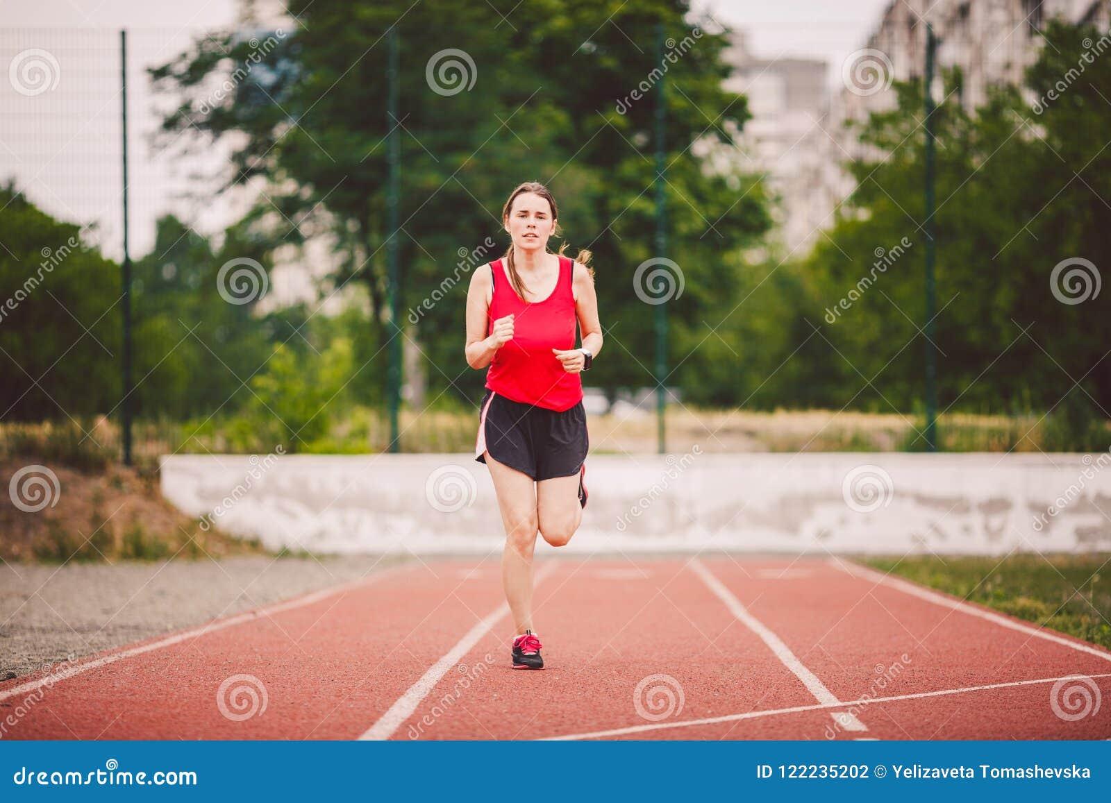 Schöne junge Athlet Caucasian-Frau mit den großen Brüsten im roten T-Shirt und in den kurzen kurzen Hosen Rütteln, laufend in das