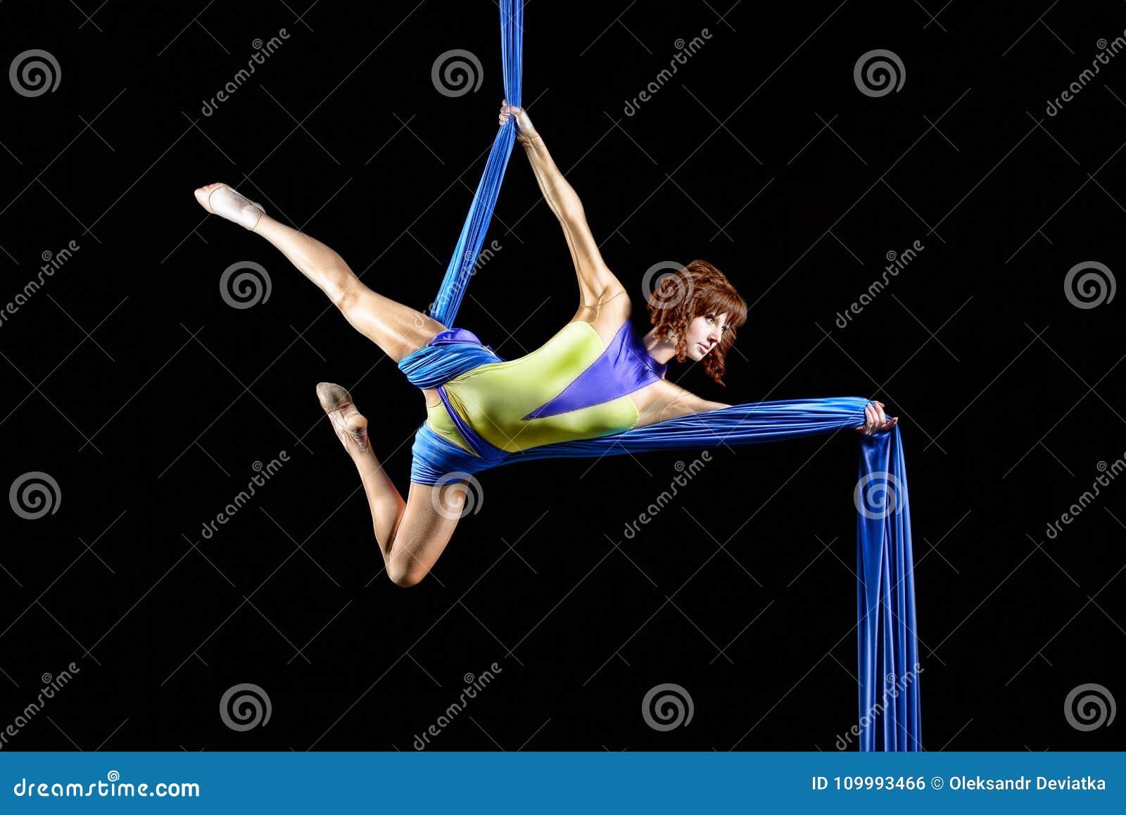 Schöne Junge, Berufsluftzirkuskünstler der athletischen sexy Frau mit Rothaarigen im gelben Kostüm, das Diagonale in der Luft auf