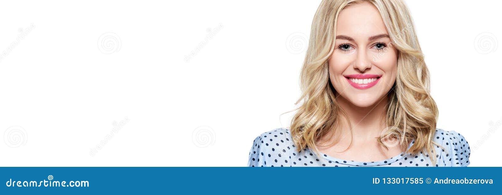 Schöne junge blonde lächelnde Frau mit der sauberen Haut, natürlichem Make-up und perfekten weißen den Zähnen lokalisiert über we