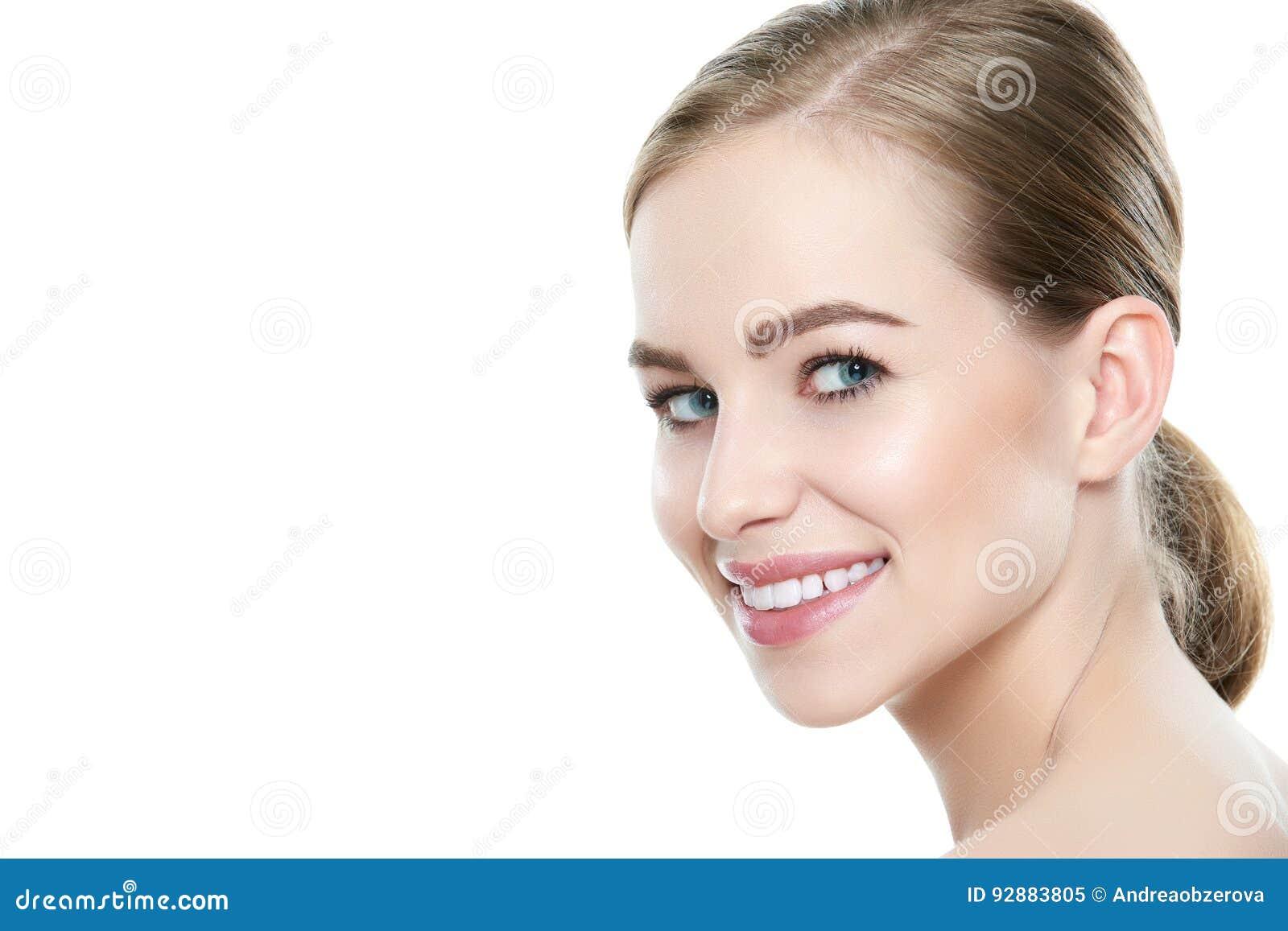 Schöne junge blonde lächelnde Frau mit sauberer Haut, natürliches Make-up und vervollkommnet weiße Zähne