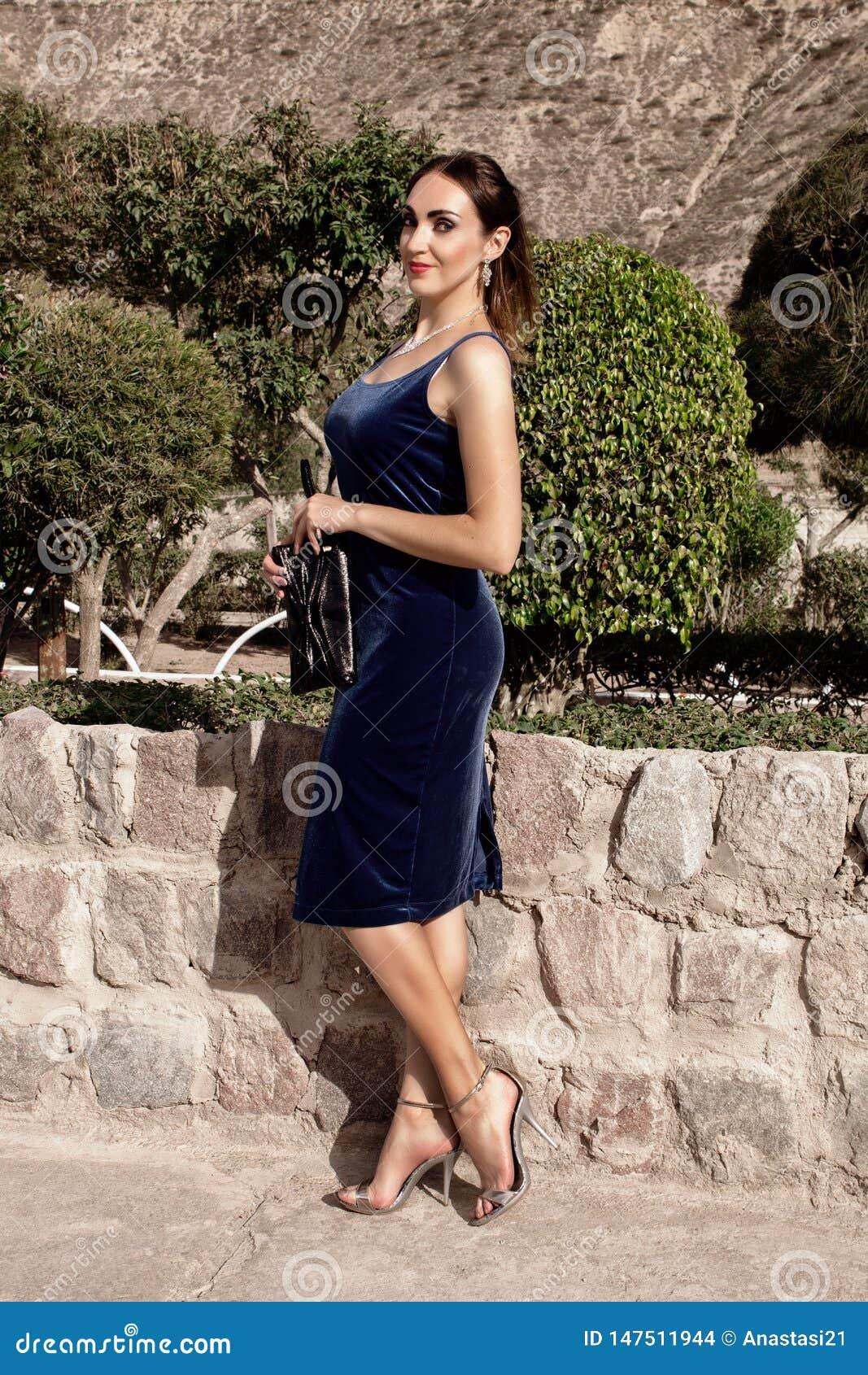 Schöne junge brunette Frau in einem blauen Abendkleid des Samts mit einer Kupplung, werfend in der Natur auf