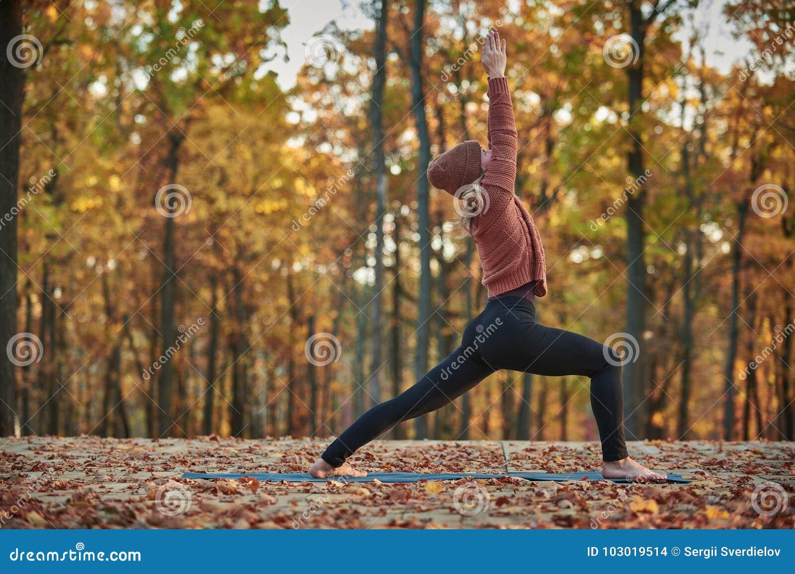 Schöne junge Frau übt Yoga asana Virabhadrasana 1 - Kriegershaltung auf der hölzernen Plattform im Herbstpark