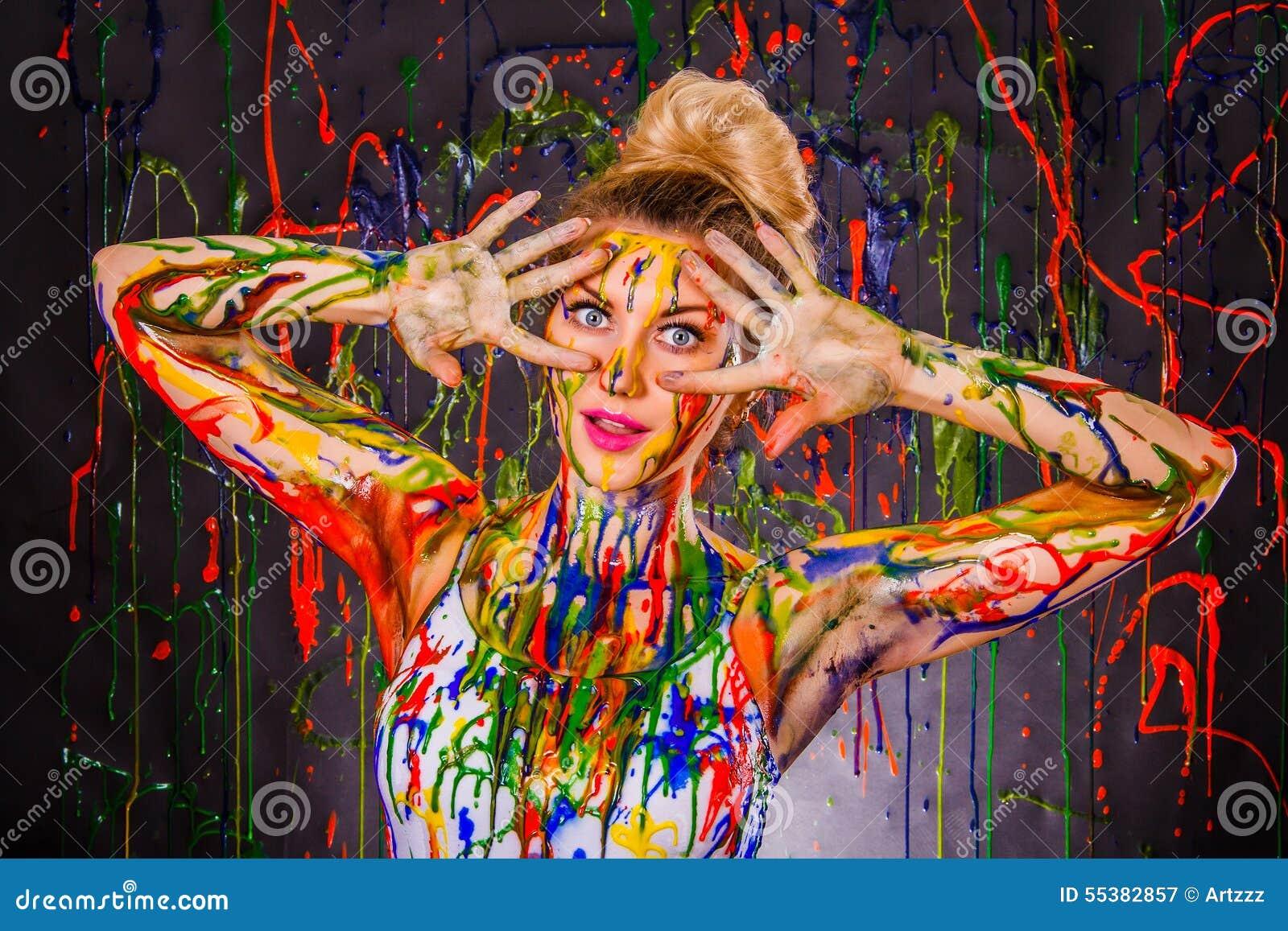 Schöne junge Frau bedeckt mit Farben