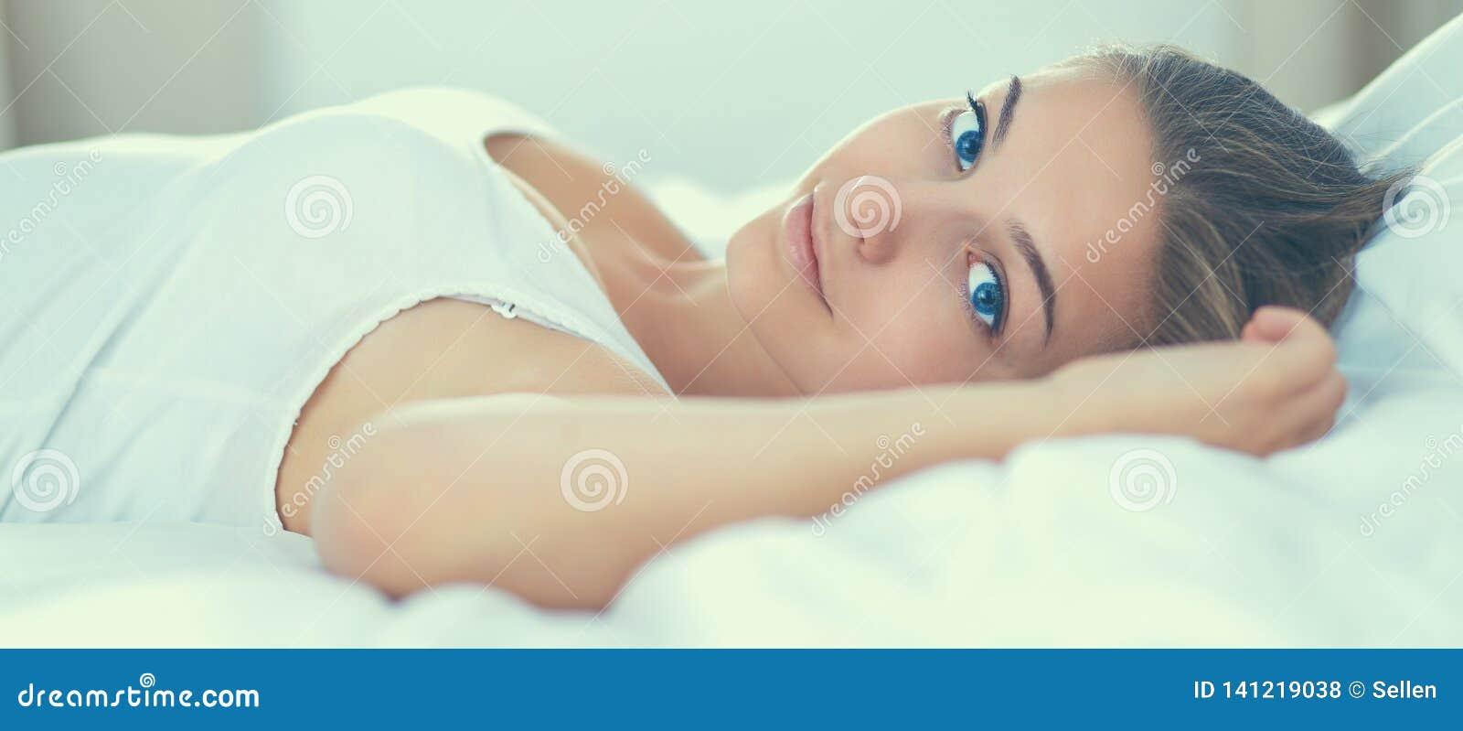 Schöne junge Frau bequem und, die himmlisch im Bett liegt