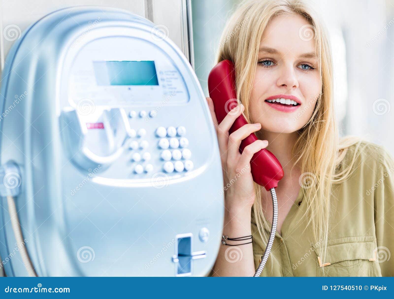 Schöne junge Frau, die über ein allgemeines Münztelefon spricht Glücklicher Ausdruck