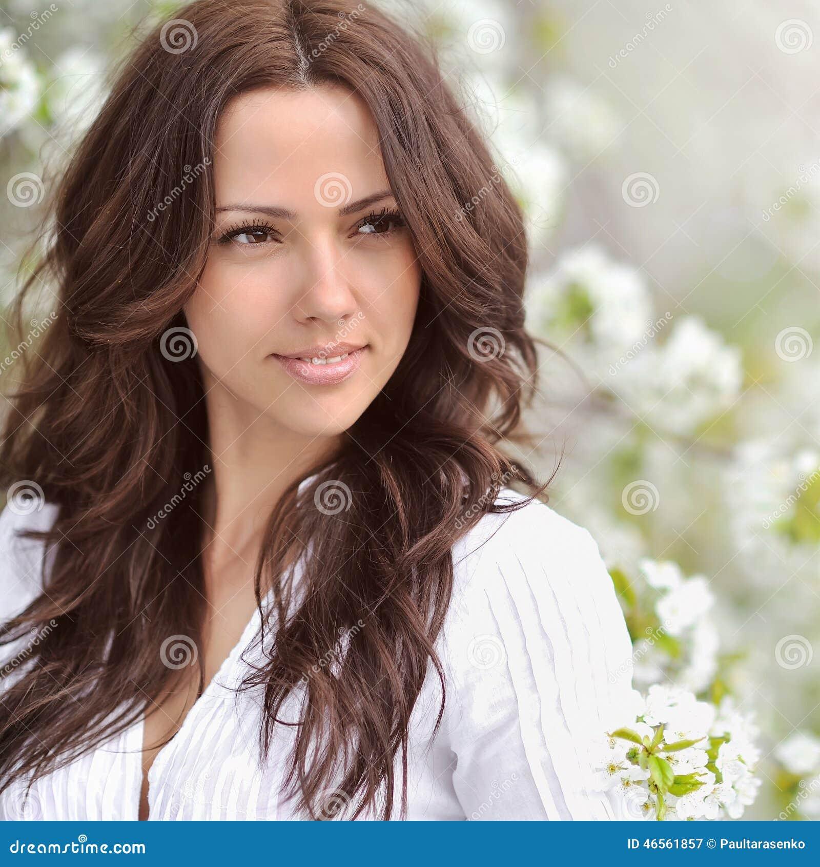 Schöne junge Frau, die auf dem grünen Gras im Freien liegt Schöne junge Frau in einem Sommerpark übertreffen