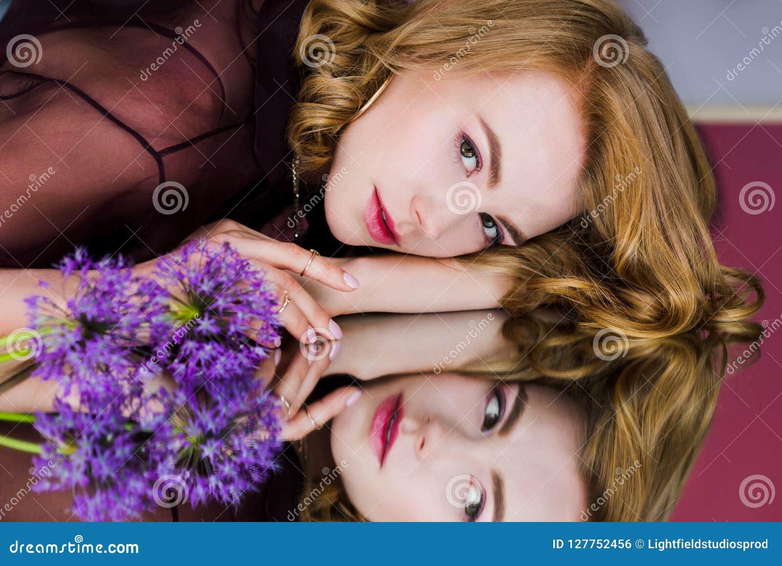 Schöne junge Frau, die auf Spiegel mit blauen Blumen und dem Schauen liegt