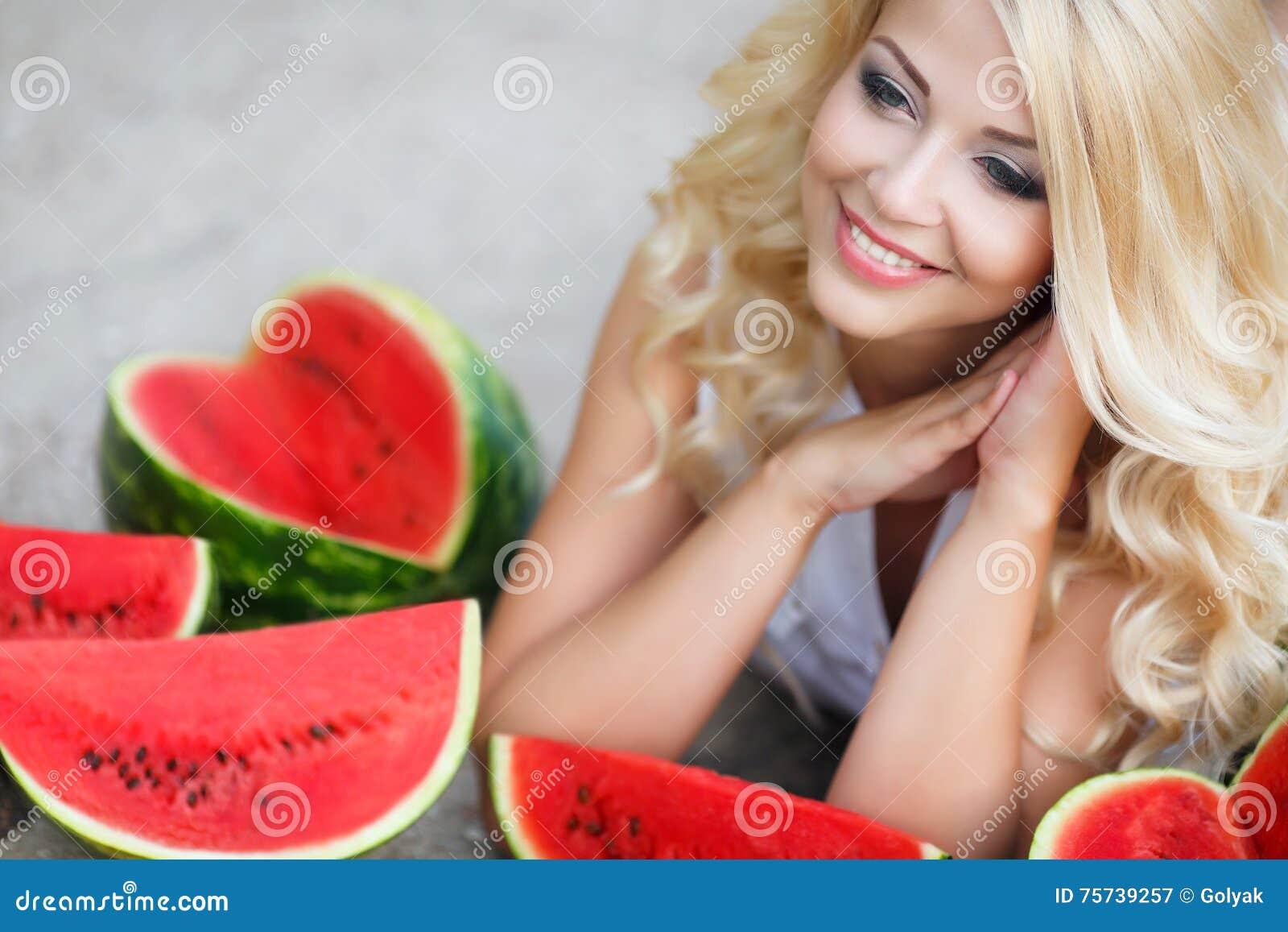 Schöne junge Frau, die eine Scheibe der reifen Wassermelone hält