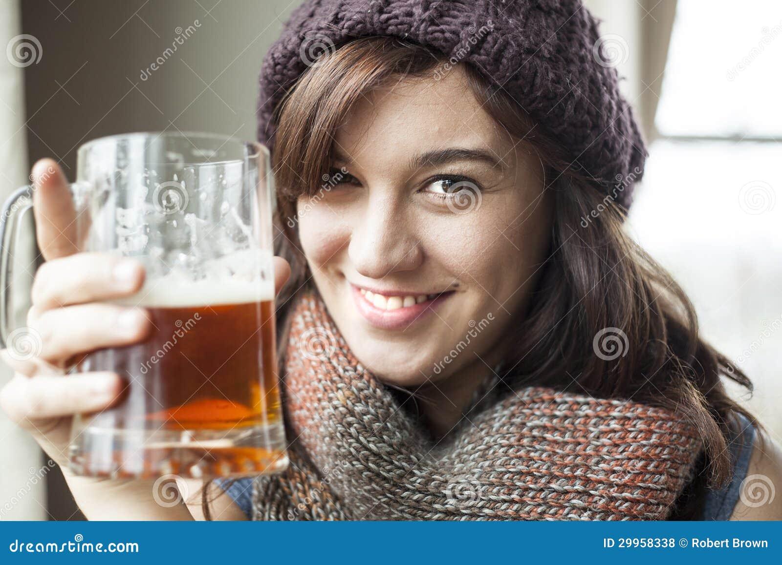 Schöne junge Frau in gestricktem Schal-und Hut-Getränk-Bier