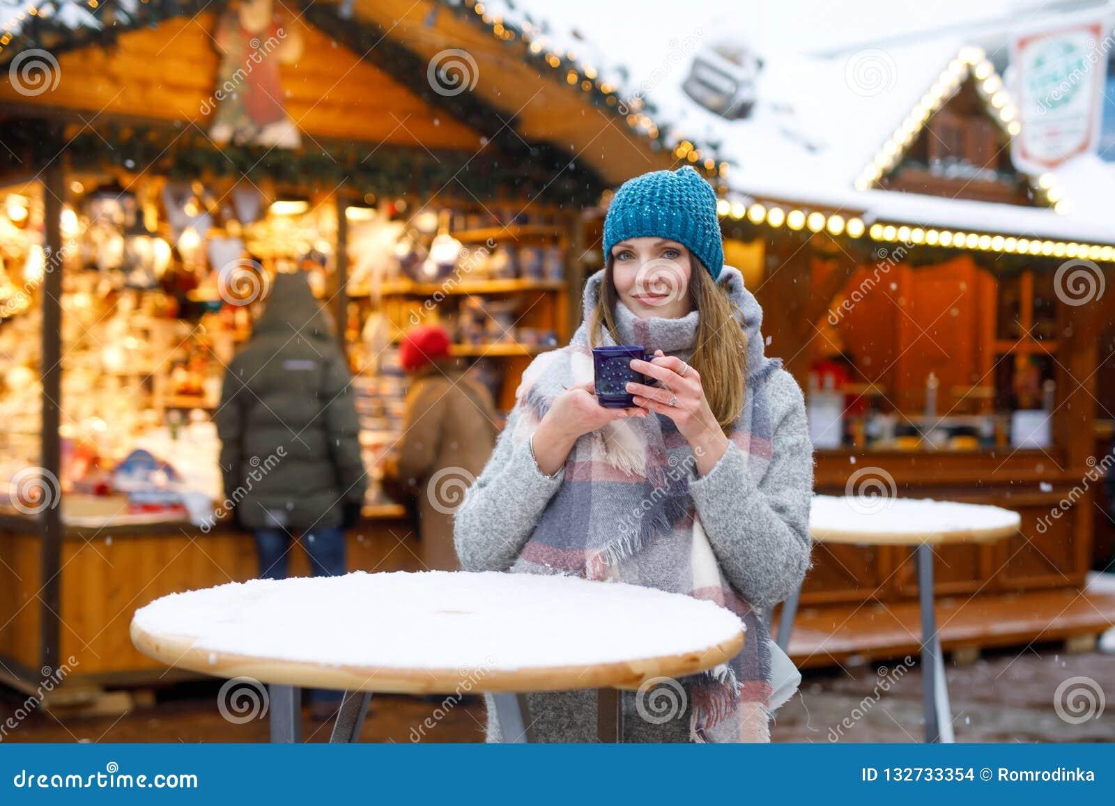 Schöne junge Frau, die heißen Durchschlag, Glühwein auf deutschem Weihnachtsmarkt trinkt Glückliches Mädchen in der Winterkleidun