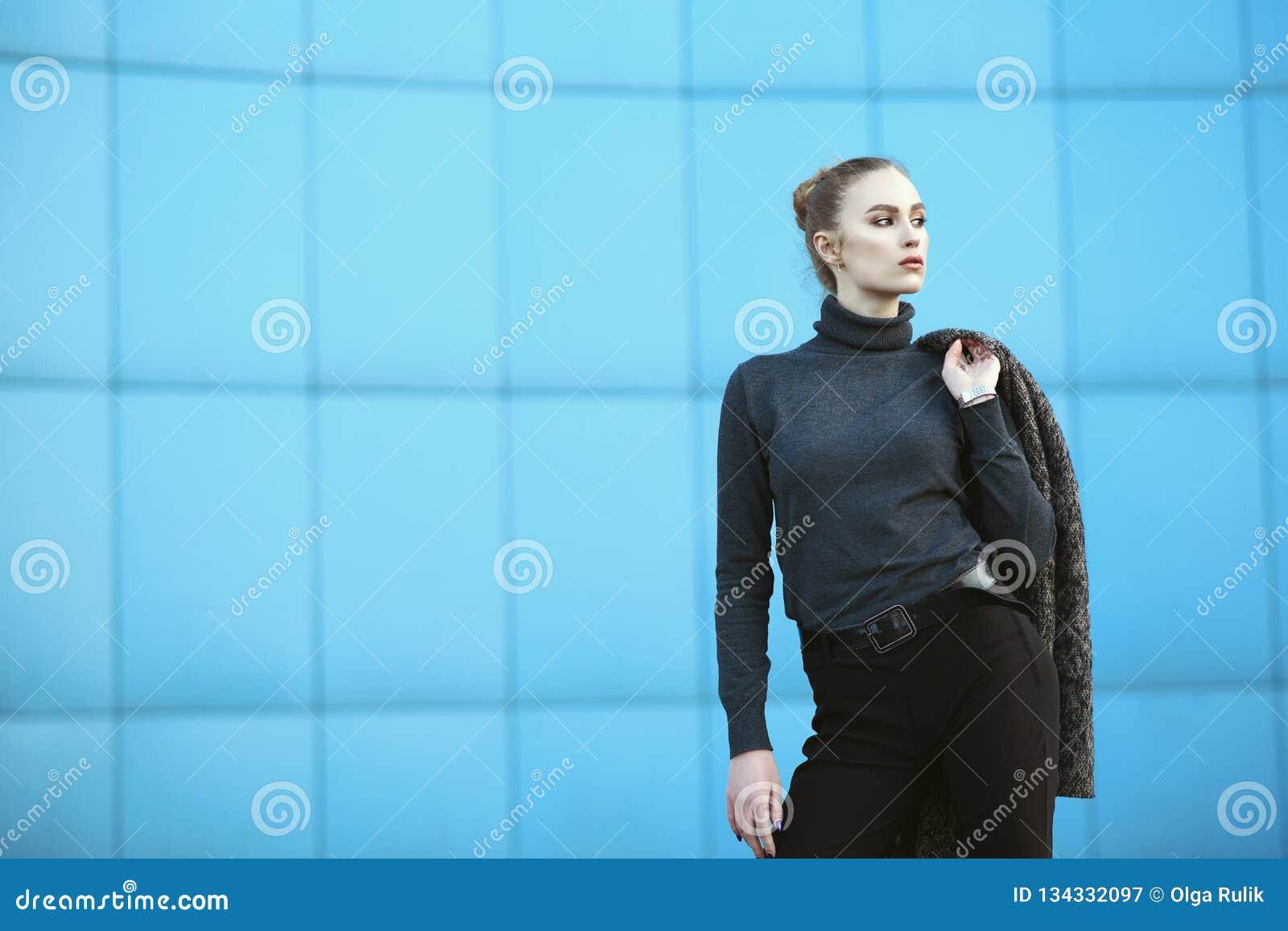 Schöne junge Frau, die ihre Jacke hinter der Schulterstellung vor blauer Wand des Stadtmalls hält