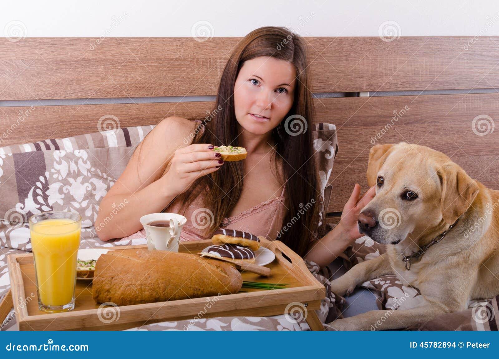 sch ne junge frau die morgens fr hst ck im bett mit hund isst stockfoto bild von espresso. Black Bedroom Furniture Sets. Home Design Ideas