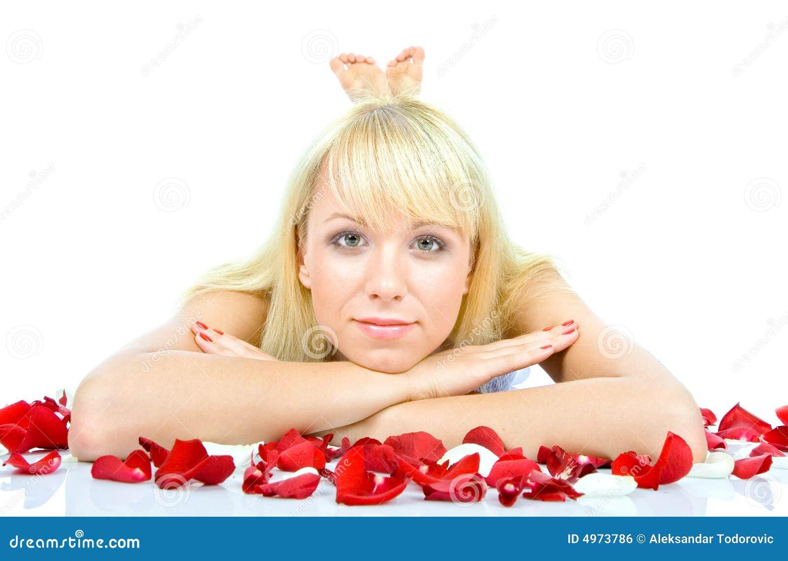 Schöne junge Frau, die rosafarbene Blumenblätter wirft