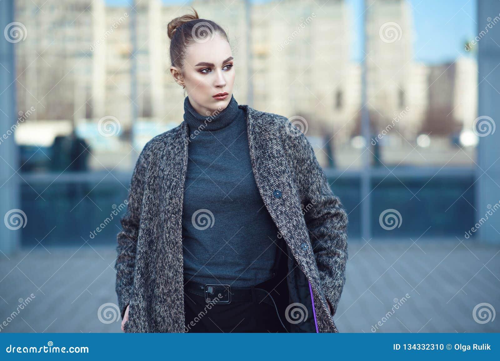 Schöne junge Frau, die am widergespiegelten Fenster des Stadtmalls geht